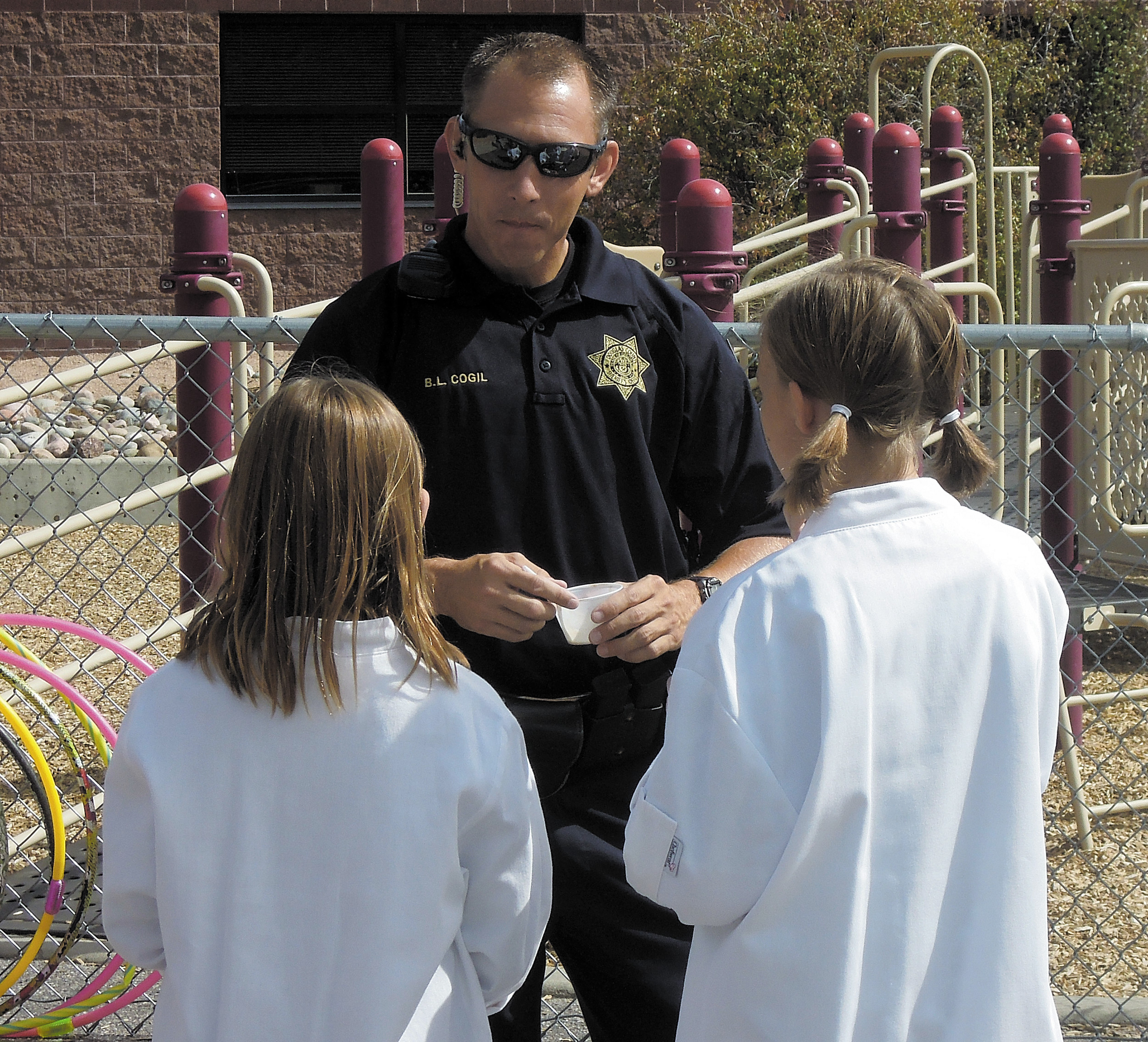 Douglas County Sheriff's Deputy Brian Cogil talk with students at Cougar Run Elementary during a fall 2013 event. Cogil is among the many officers who frequently visit schools as part of DCSD's marshal program. Photo by Jane Reuter