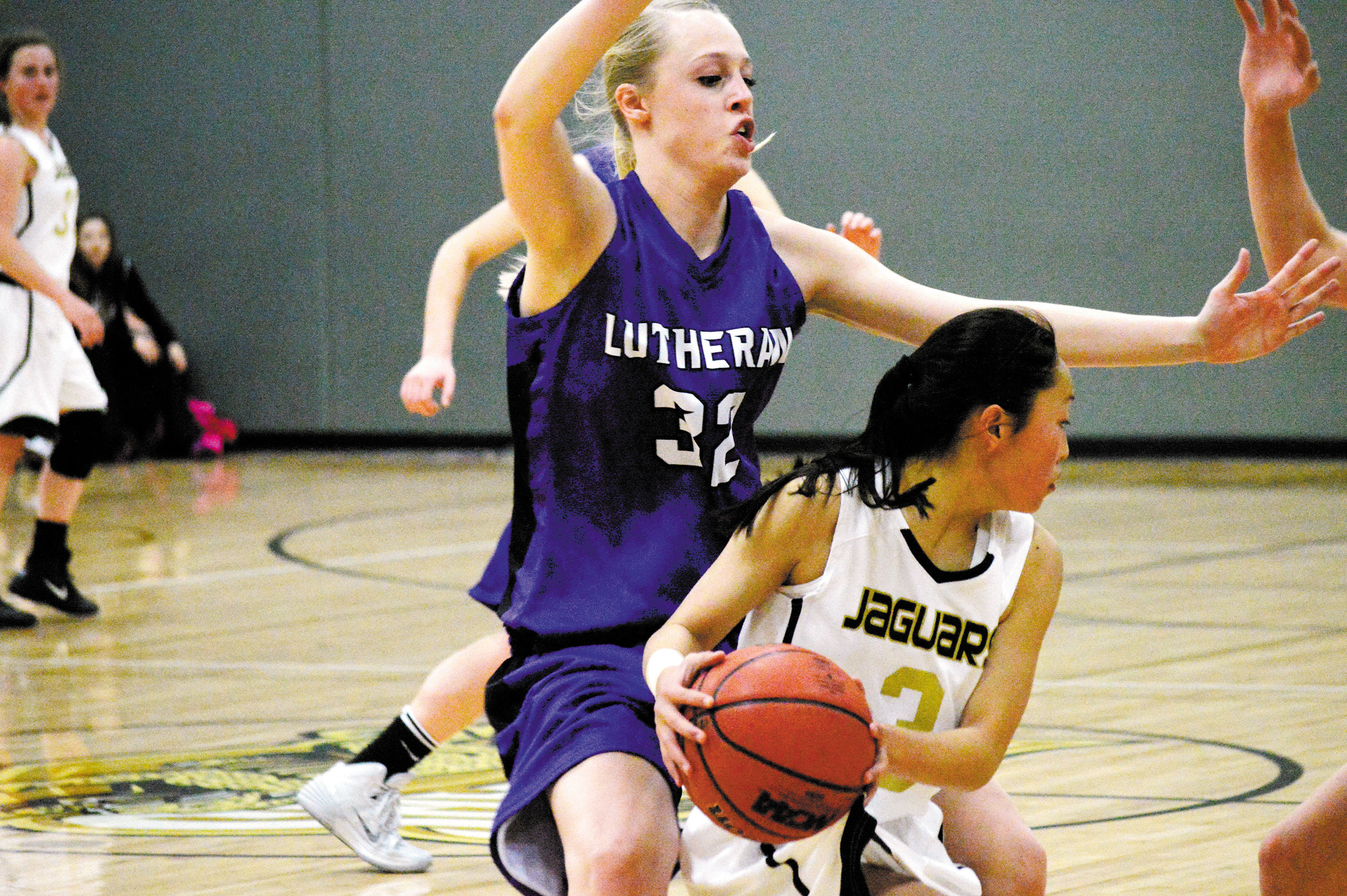 Lutheran's Cara Thomas, left, guards Jefferson Academy's Kristi Nagai, right Jan. 22 at Jefferson Academy High School. Thomas led the Lions with 19 points in the team's 49-46 victory.