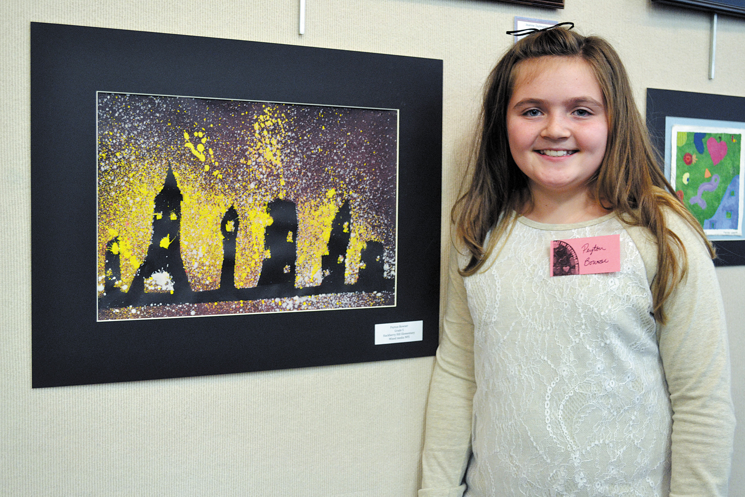 Peyton Bowser, a fifth-grade student at Hackberry Hill Elementary School, stands next to her purple and black cityscape artwork at the Art for the Young at Heart Artist Reception, Feb. 12.