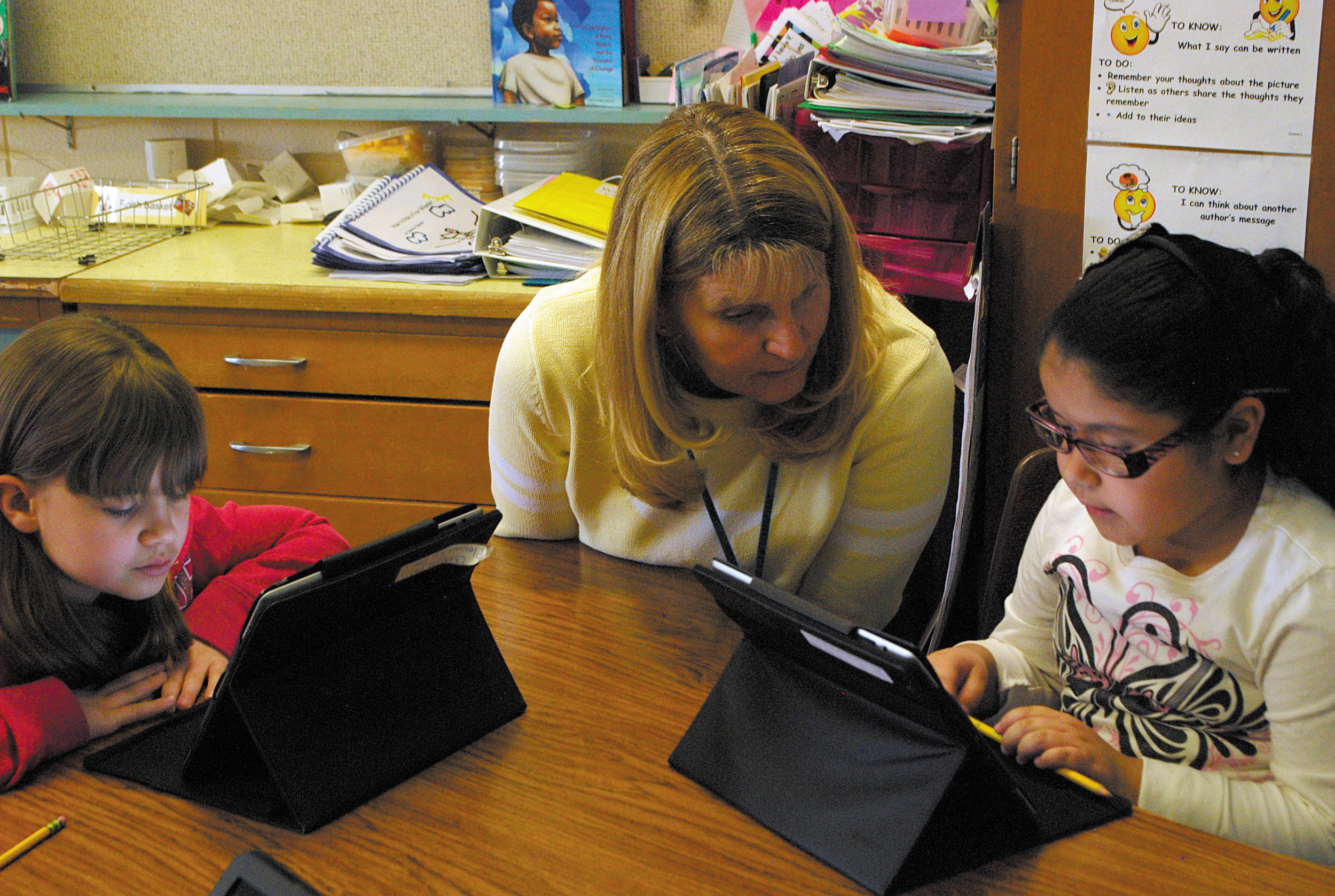 Leslie Ortiz-Lopez, left, and Cindy Villaba, far right, sit at the iPad station with their teacher Mrs. Parrish to read a book followed by discussion and assignments related to their reading.