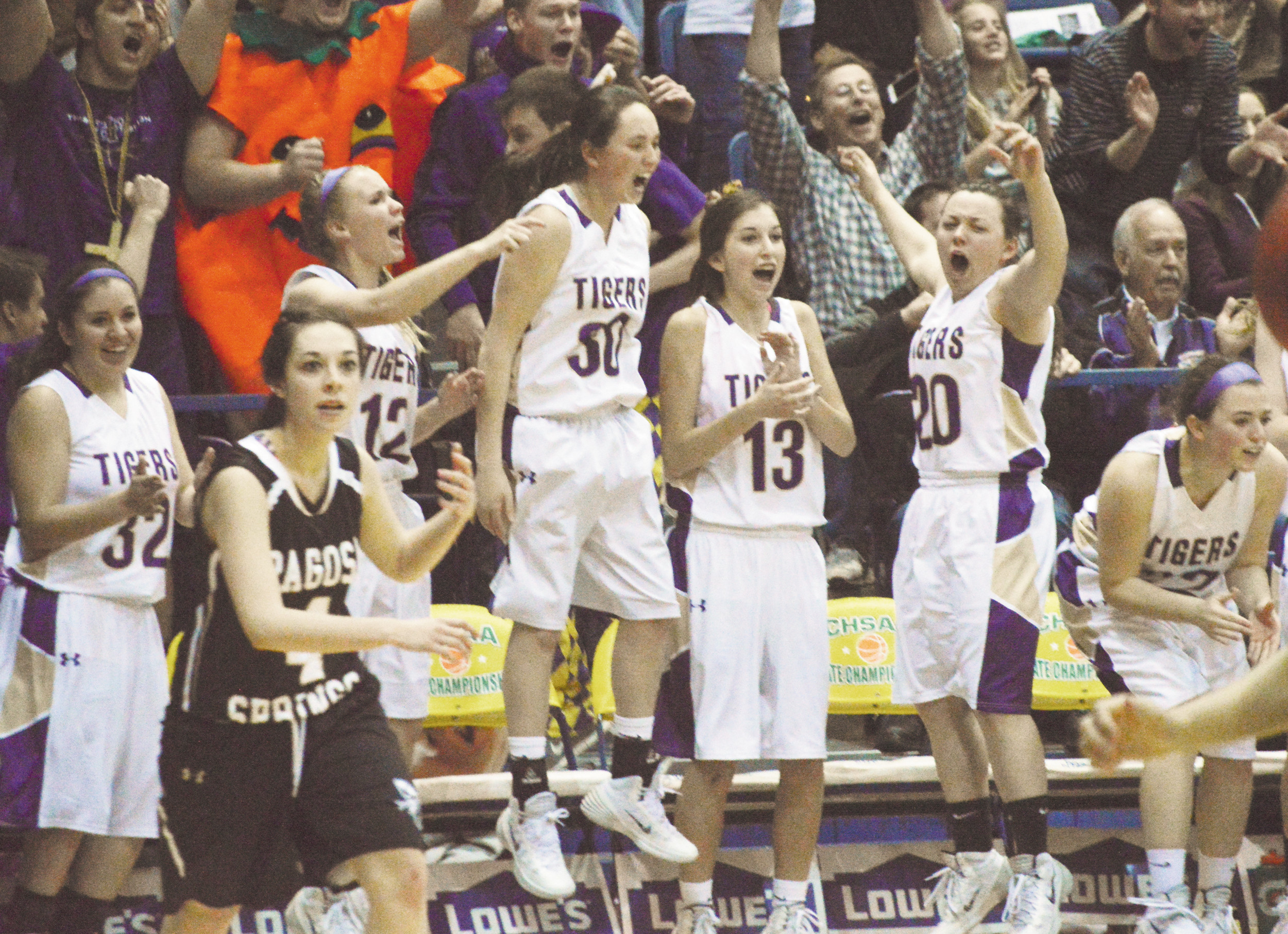 The Holy Family bench celebrates after the Tigers scored late in the fourth quarter of the championship game of the 3A Girls Basketball State Tournament against Pagosa Springs March 15 at the Air Force Academy's Clune Arena.