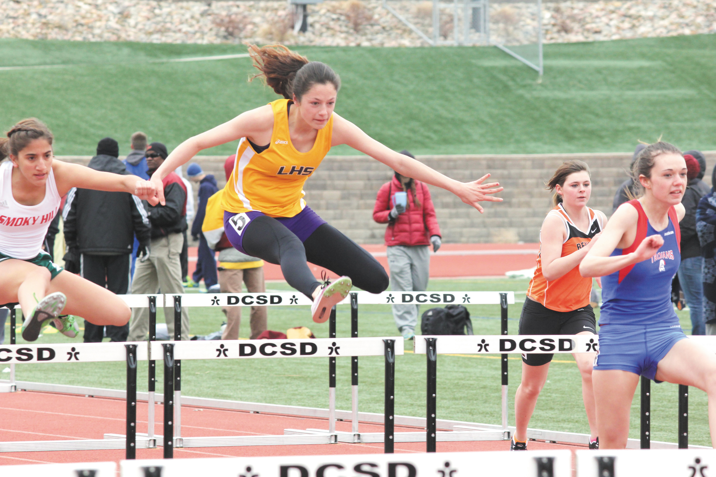 Littleton's Victoria Dinkel clears the barrier in the 100-meter hurdles at the March 22 Sabercat Invitational. Dinkel finished third in her heat in the hurdles and later helped the Lions finish second in the 800-meter sprint relay.