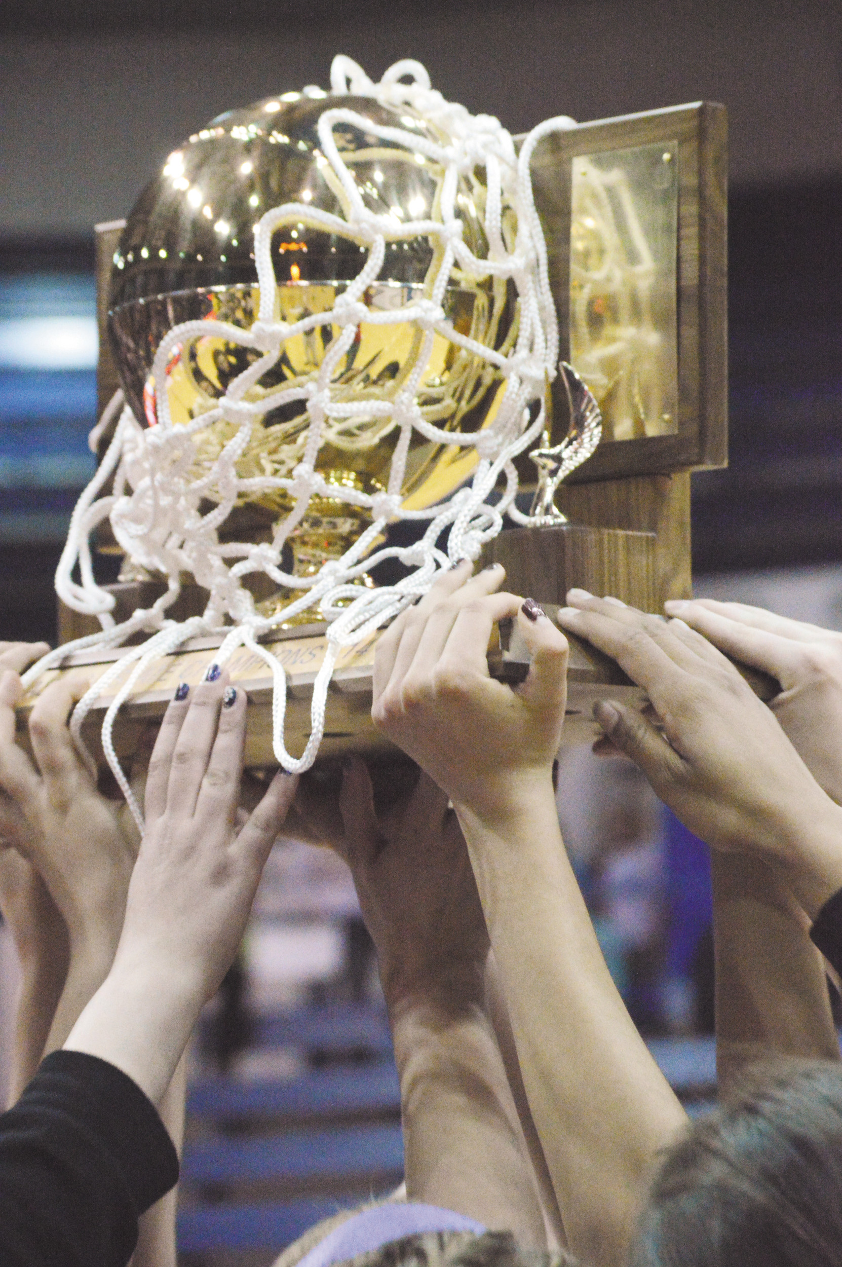The Holy Family girls team hold up the trophy after winning the championship game of the 3A Girls Basketball State Tournament against Pagosa Springs March 15 at Air Force Academy's Clune Arena.