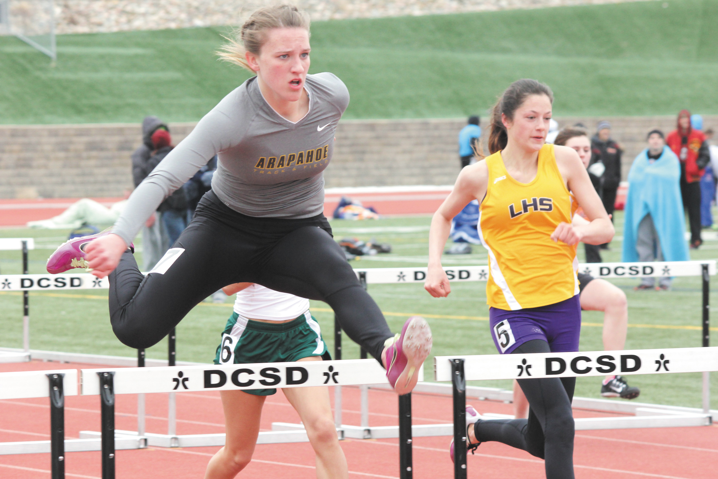 Lilly Boettcher of Arapahoe clears a hurdle ahead of Littleton's Victoria Dinkel in the 100-meter hurdles at the March 22 Sabercat Invitational. Boettcher finished 13th in the event but later in the meet helped the Warrior 800 sprint medley team finish third.