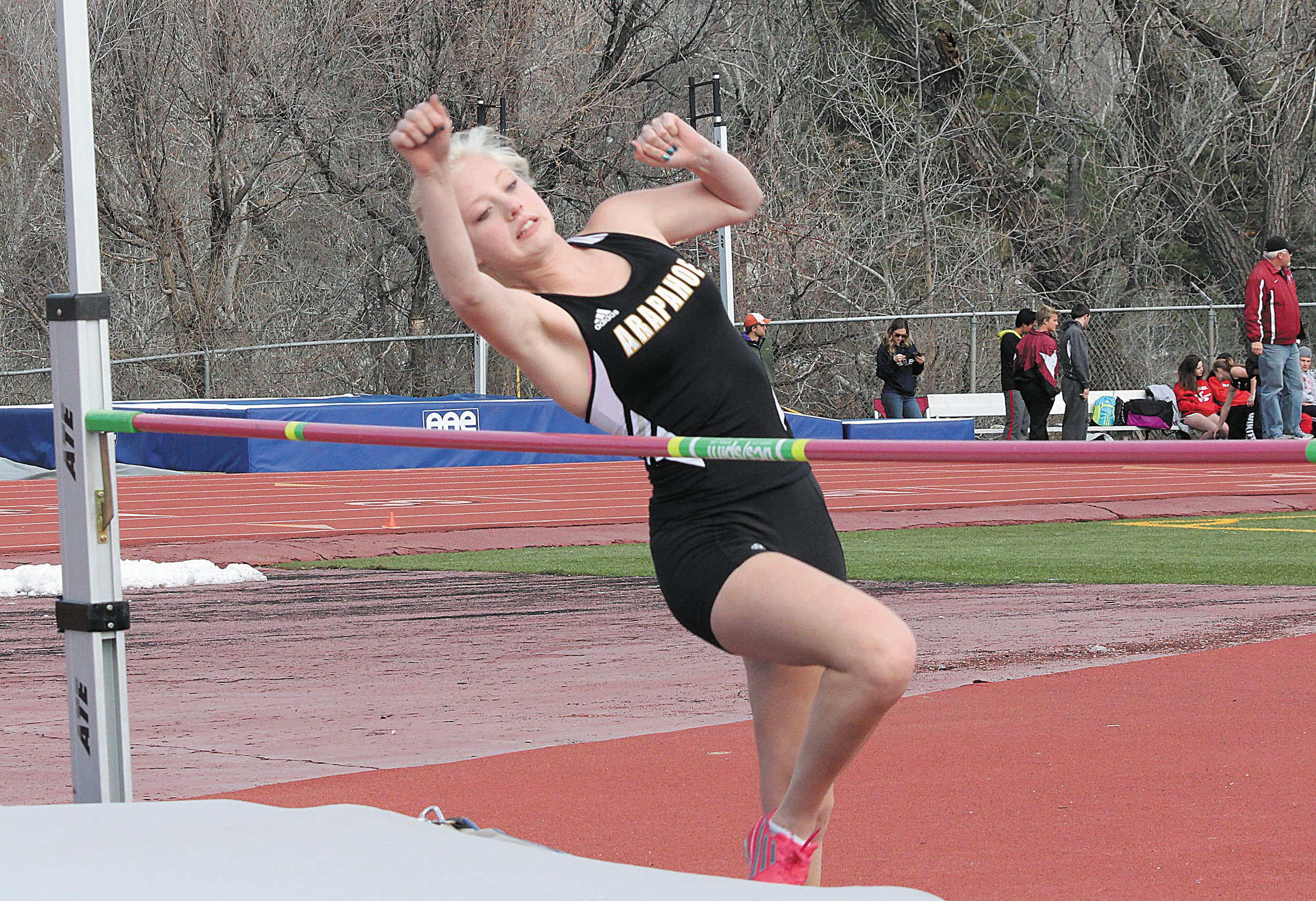 Arapahoe senior Addyson Harland goes over the bar during the high jump competition at the April 4 Littleton City Meet. The Warriors won both the boys and the girls team titles.