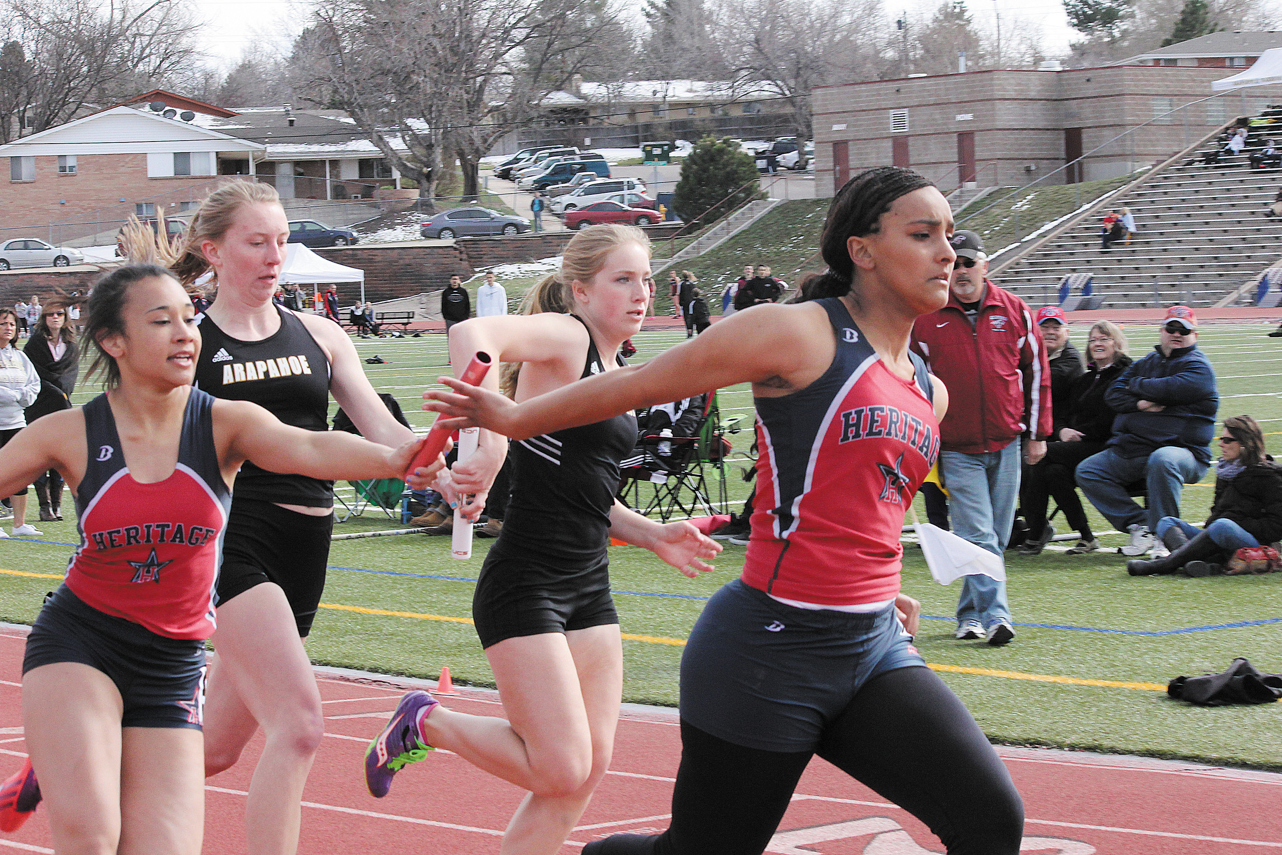 Erin Gaines, left, hands the baton to Heritage teammate Takyra LeBlanc in the 800-meter sprint medley at the April 4 Littleton City Meet. The handoff was good and the Eagles won the event.