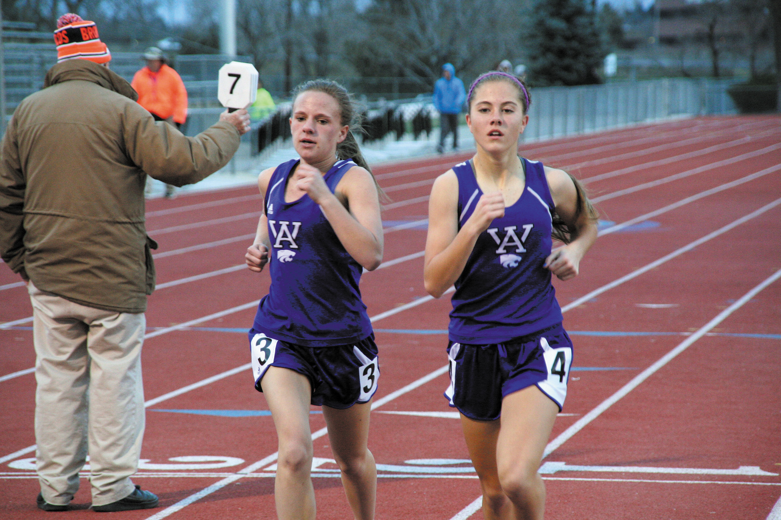 Arvada West's Erin Rawe-Thomas and Abby Kostelecky run side-by-side and stride for stride in the 3200 meter event Wednesday at Jeffco Stadium. Rawe-Thomas went on to win the race. Photo by Daniel Williams