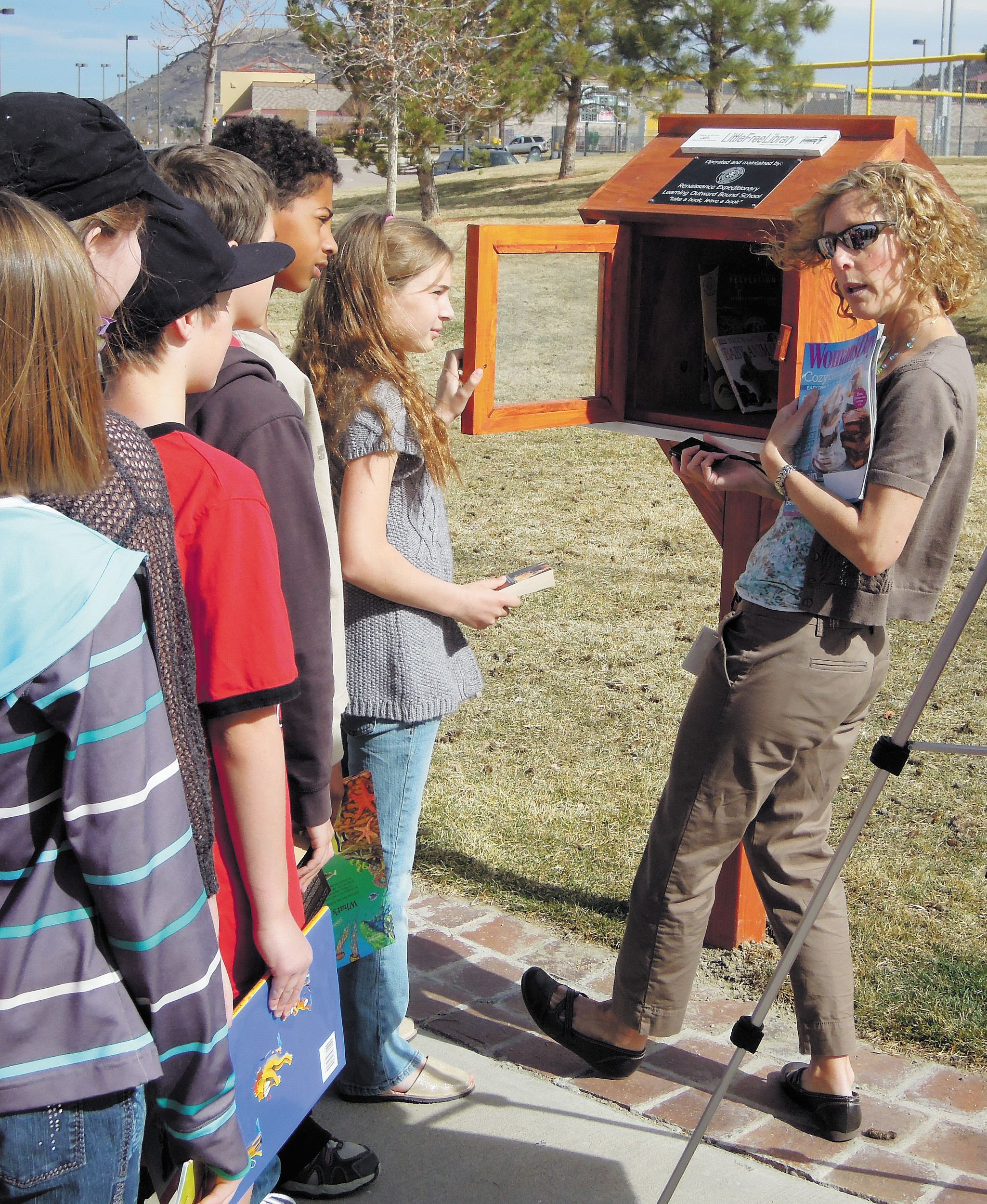 Teacher Diana Hyland demonstrates the newly installed Little Free Library as her students wait to fill it with books. Renaissance Expeditionary School students coordinated the project at Castle Rock's Metzler Ranch Community Park. Photo by Jane Reuter