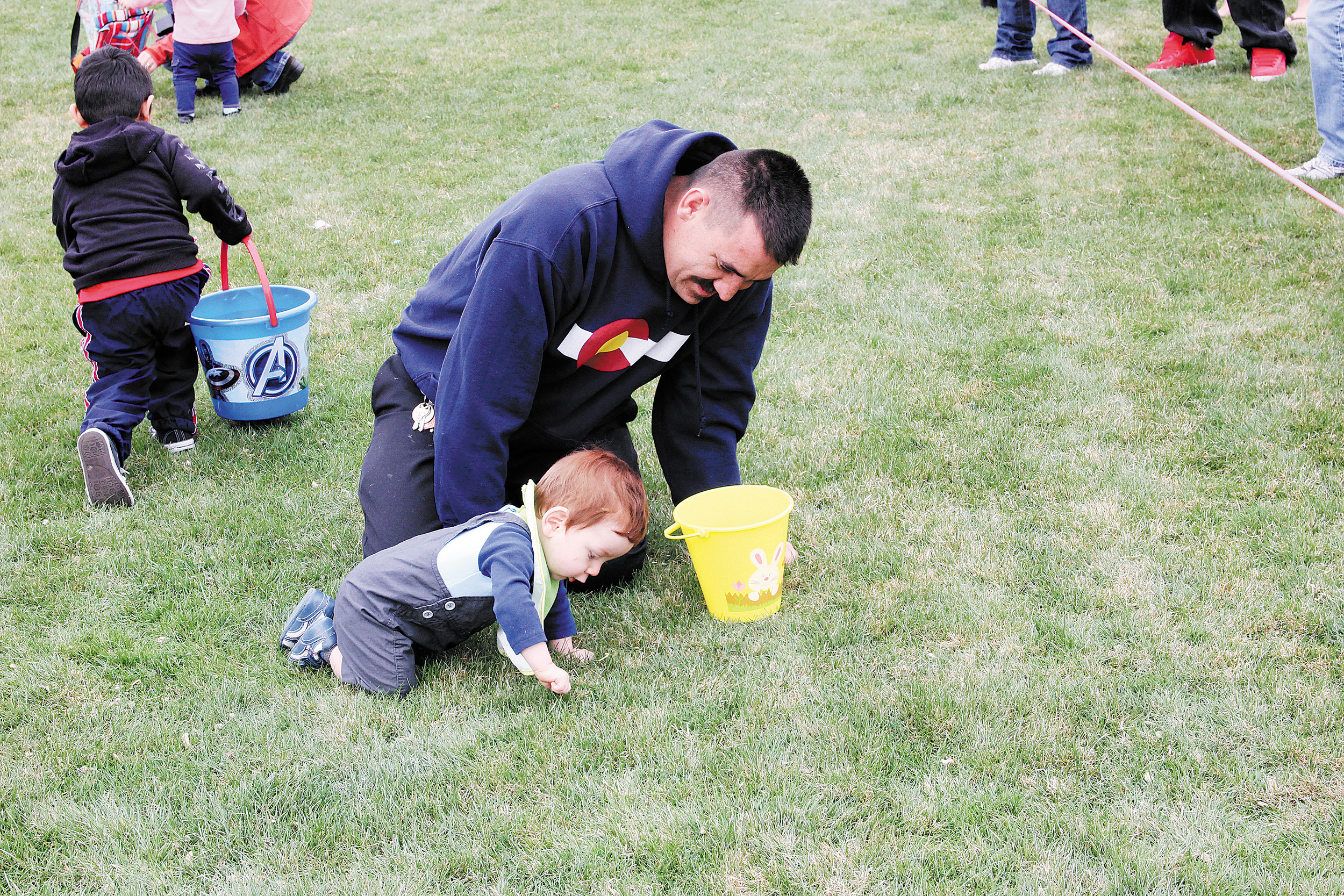 Pedro Iniguez helps his young son Eprain pick up a piece of candy. The Iniguez family joined hundreds who attended Englewood's April 12 Great Egg Scramble. Photo by Tom Munds