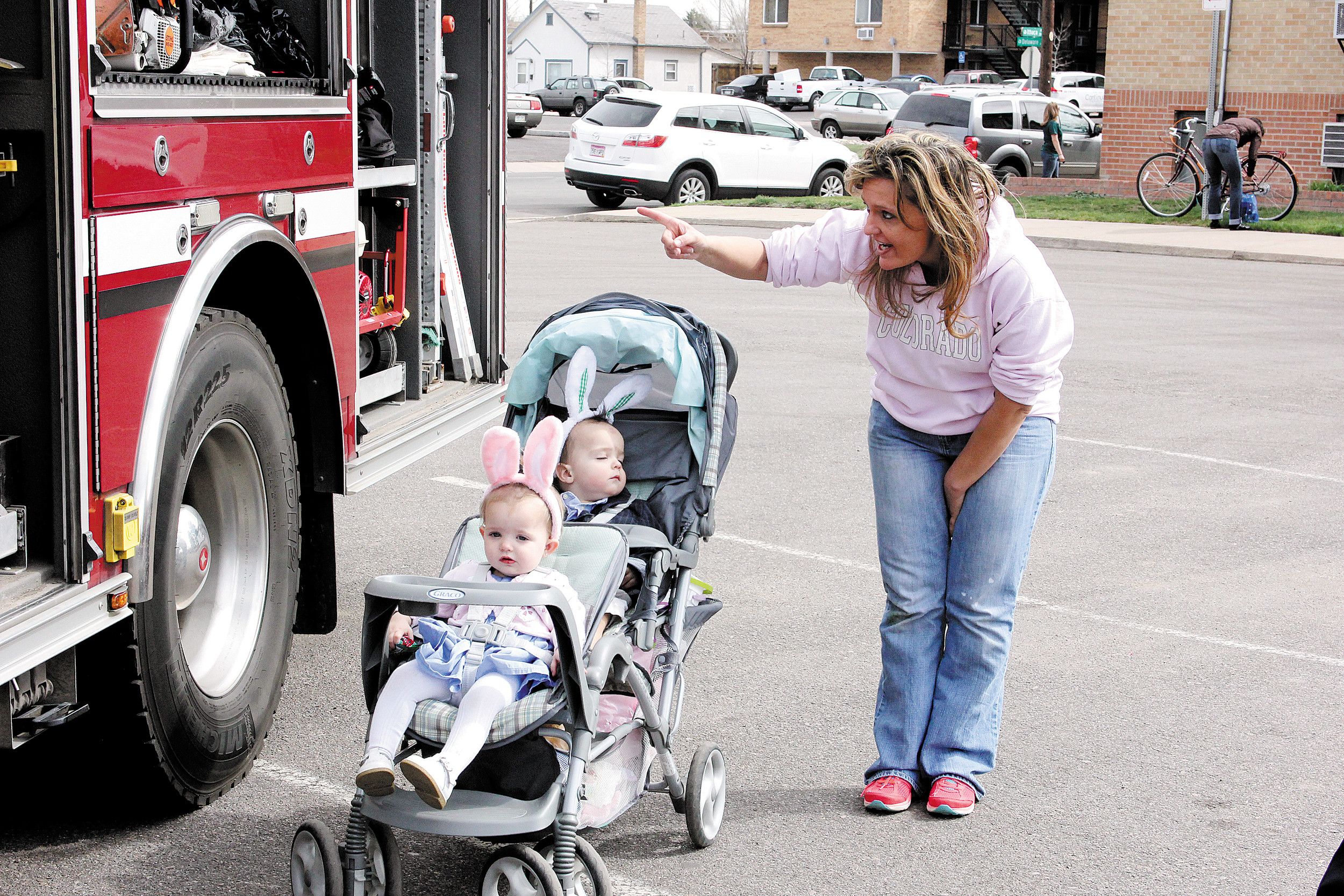Tanya Ohlinger, right, points out the items in the fire truck to her twins Hayleigh, front, and Harley. The fire truck was on display during Englewood's April 12 Great Egg Scramble. Photo by Tom Munds