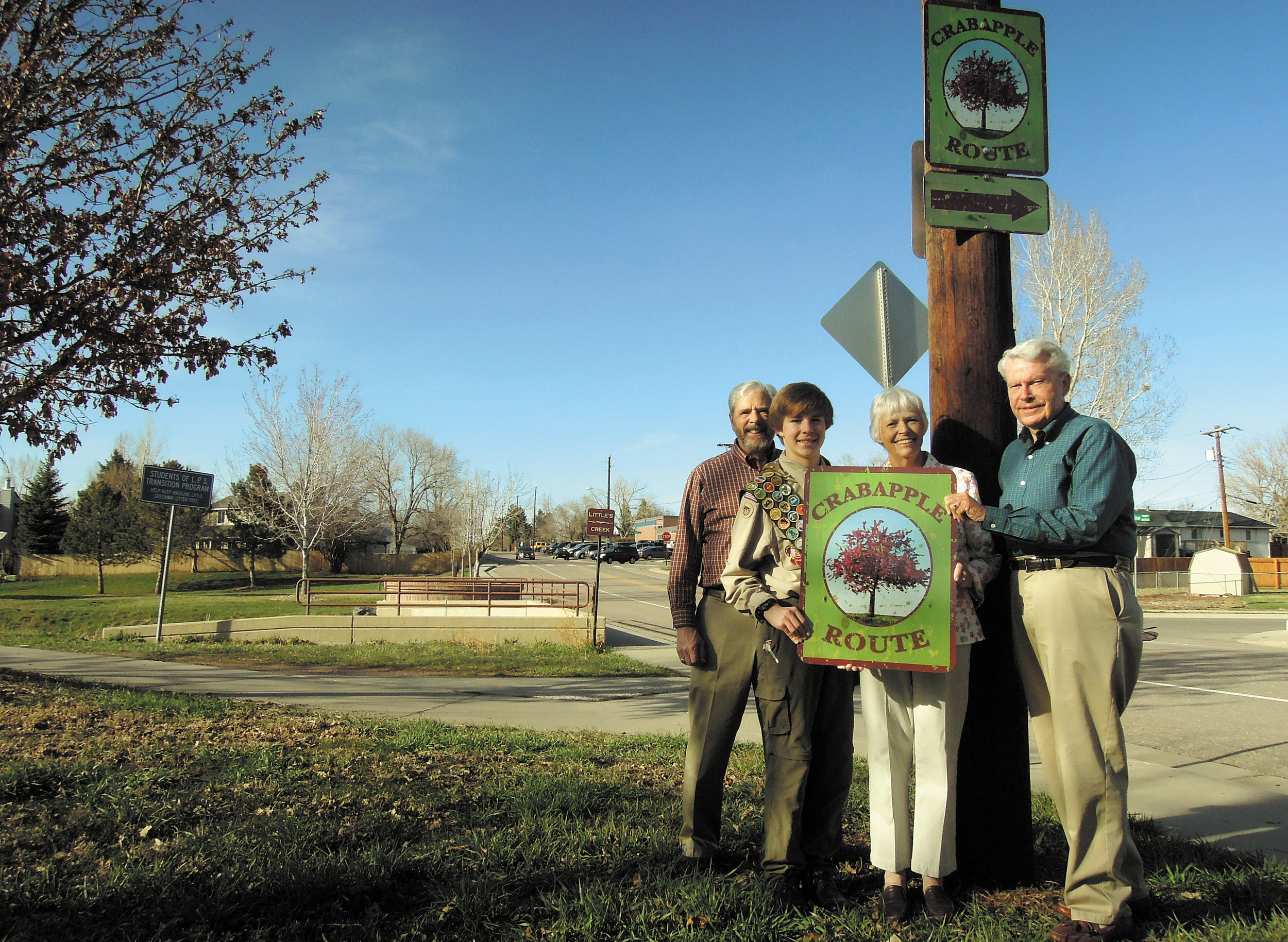 From left, Larry Borger, Cole Hancock, Mary Gardinier and Dick Dugdale display the sign the city presented to Gardinier in honor of her late husband, Vaughn, who created the city's Crabapple Trail.