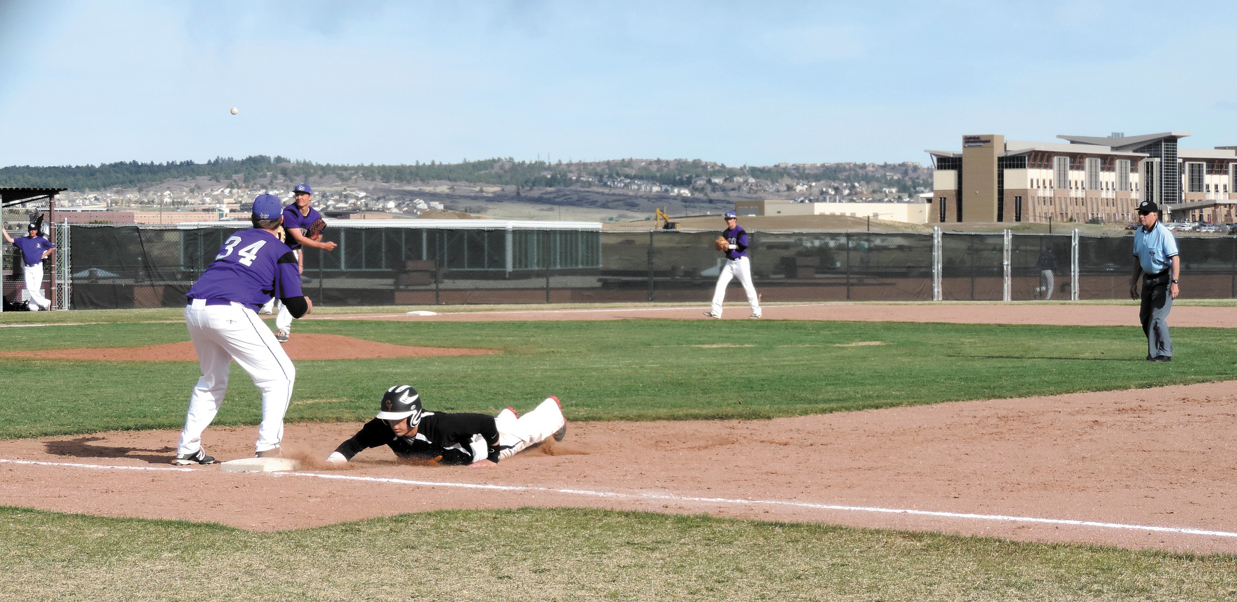 Castle View's Trevor Smeeton dives back into first base ahead of the throw to Douglas County's Brandon French (34).
