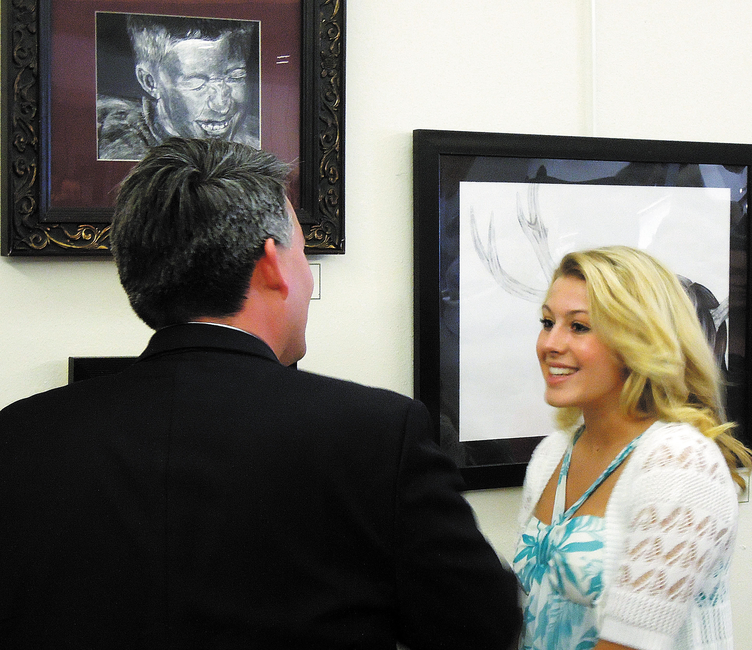 "Rock Canyon High School junior Erin Riner, right, talks with Congressman Cory Gardner about her award-winning piece, ""My Brother"" (above Gardner), at the Lone Tree Golf Club April 22."