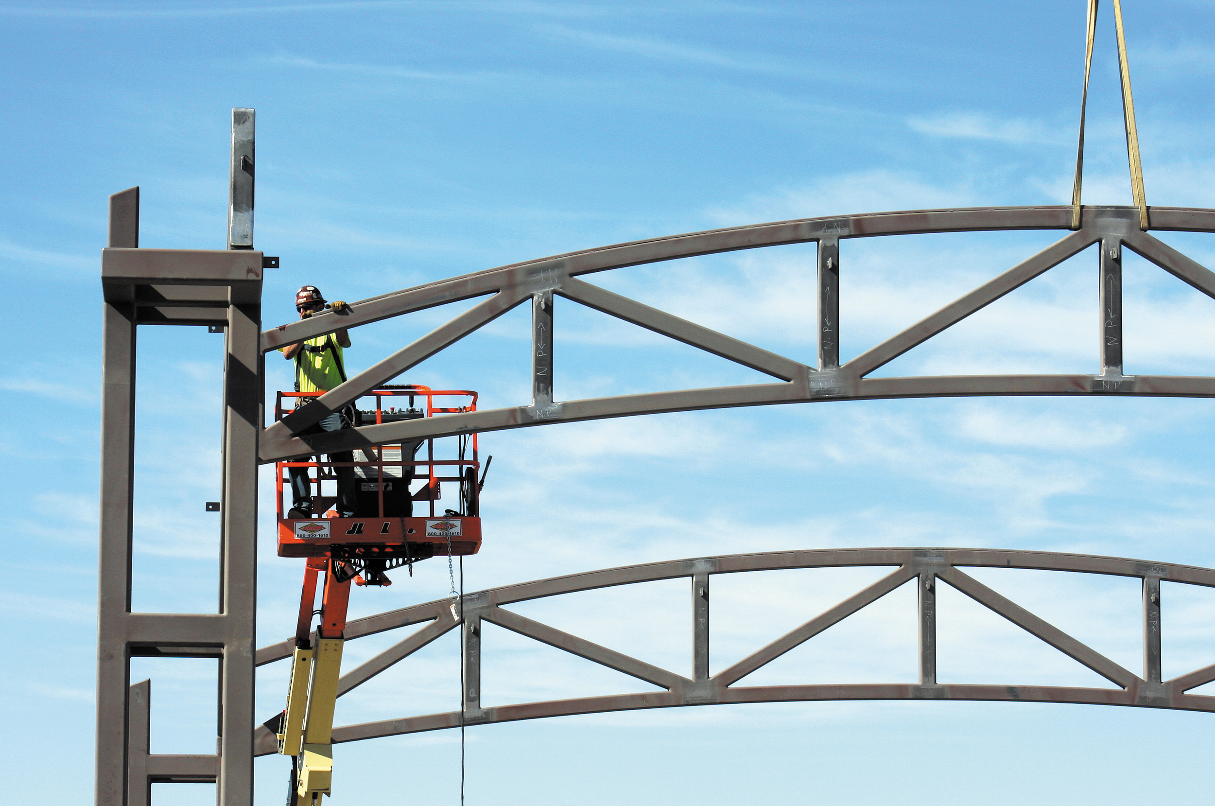 A member of the crew secures a steel truss in place atop the amphitheater at Centennial Center Park on May 2.
