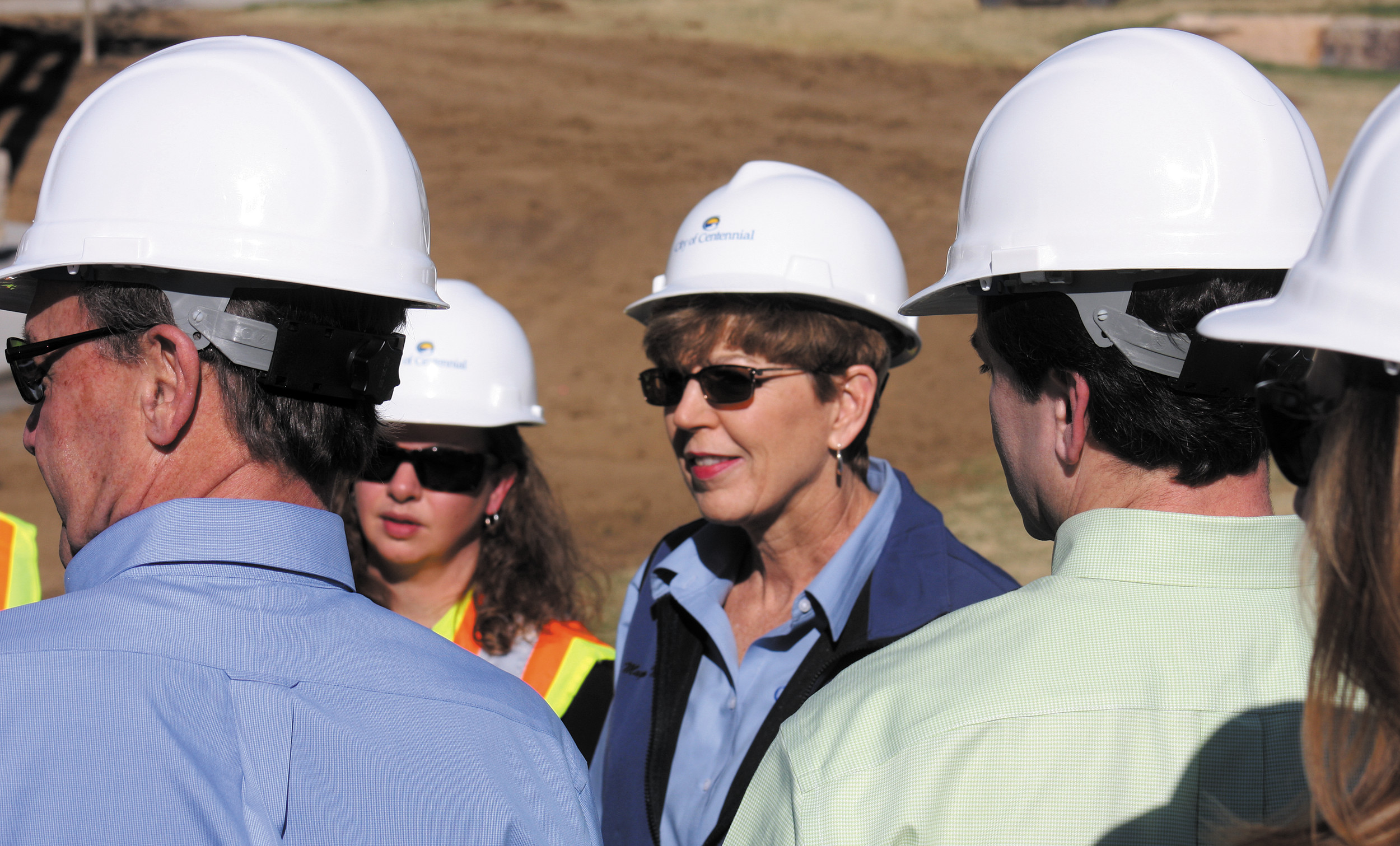 "Like all others assembled for the ""topping-off"" event, Centennial Mayor Cathy Noon, center, donned a hard hat."