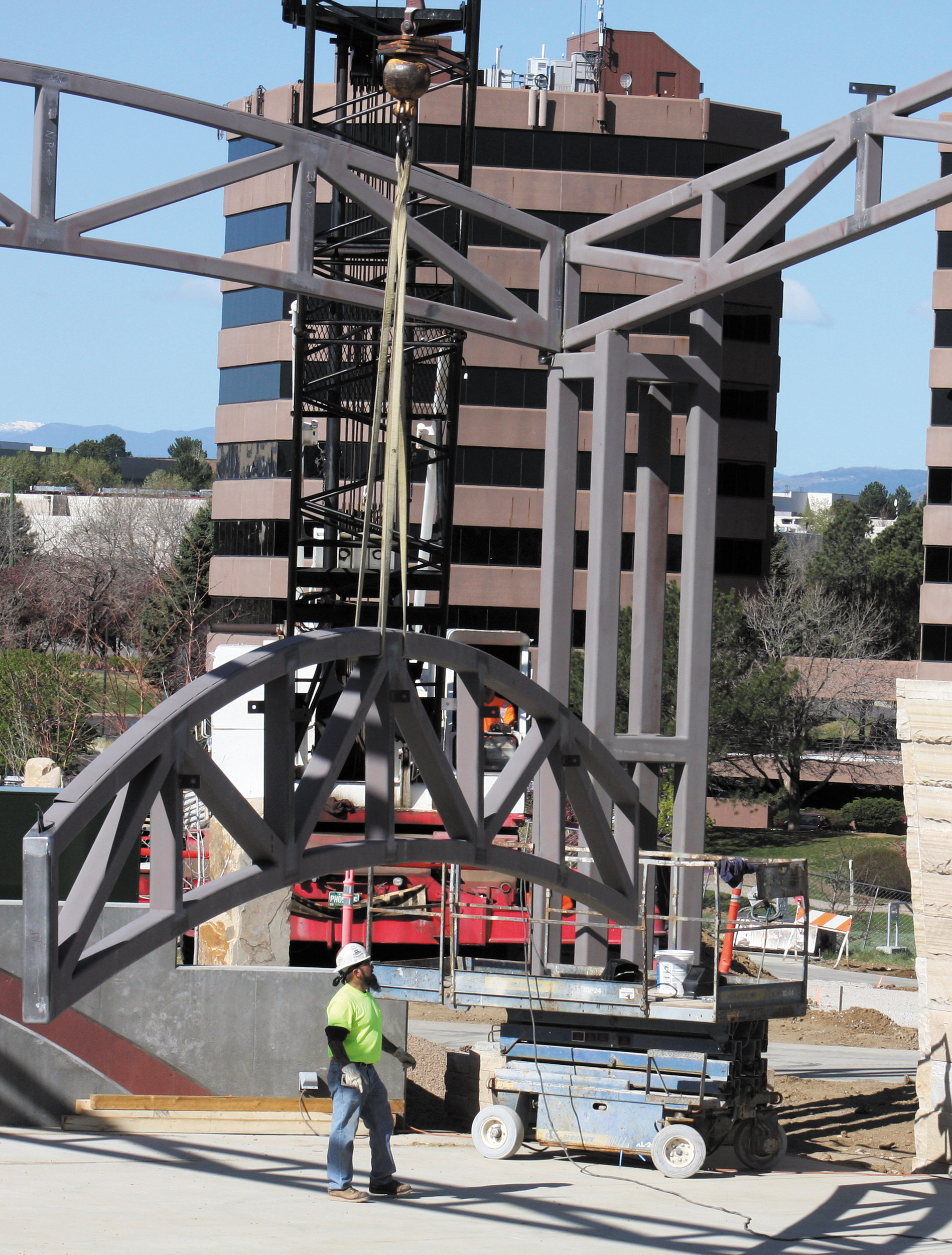 A crane hoists the steel truss up toward its permanent position atop the amphitheater at Centennial Center Park on May 2.