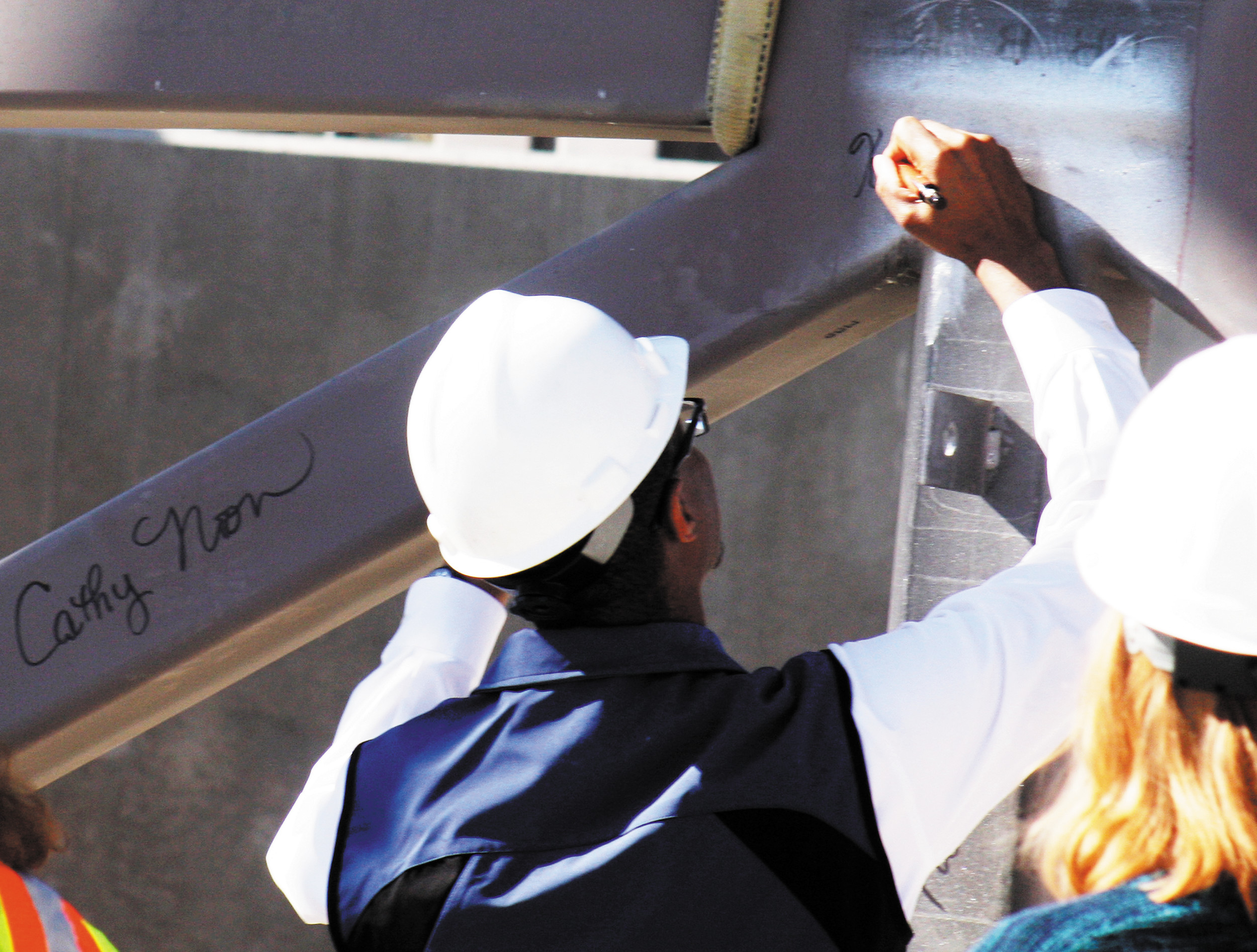 Centennial City Councilmember Keith Gardner signs his name on the truss, not far from the mayor's name to his left.