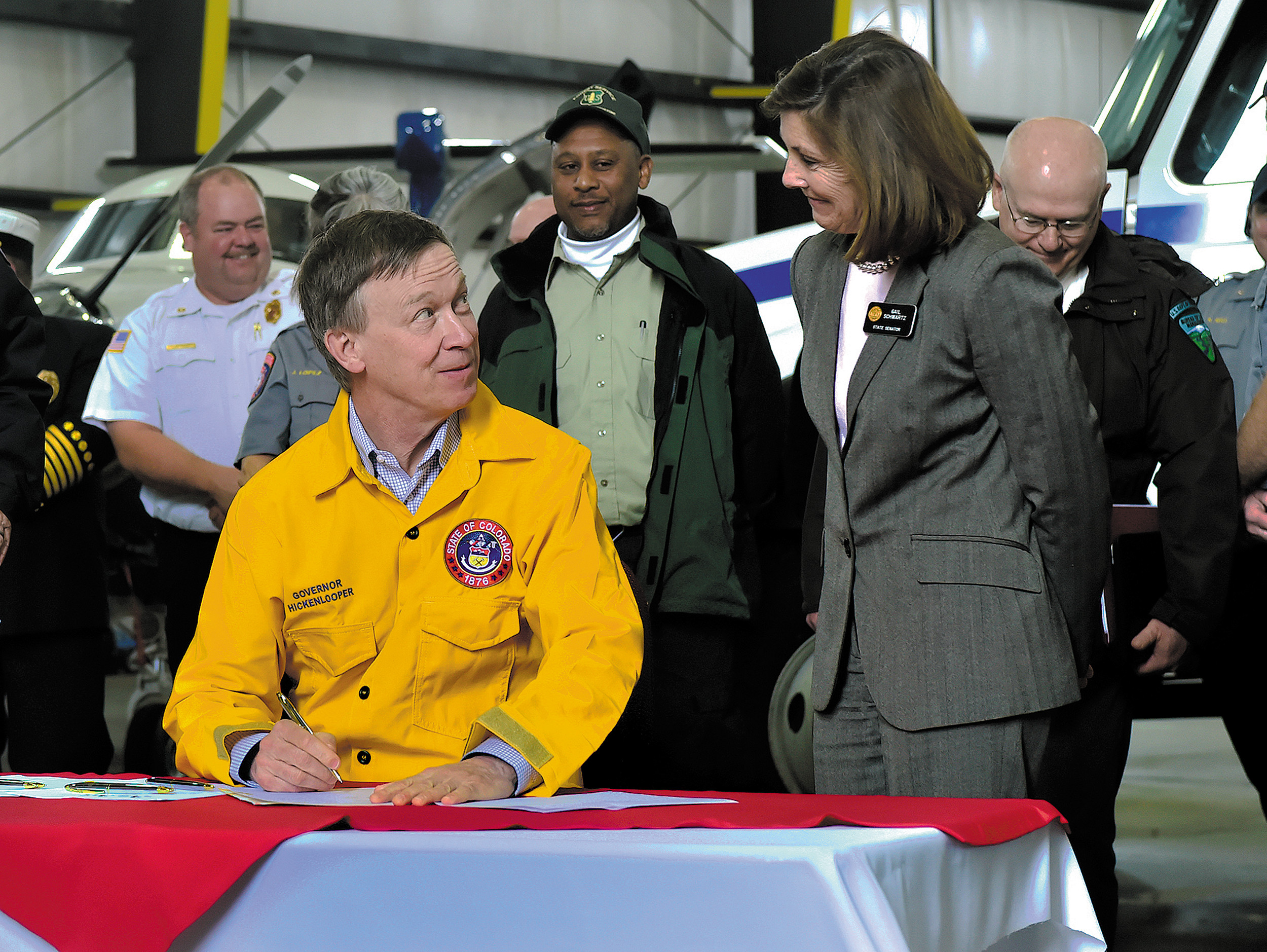 "Gov. John Hicklenlooper prepares to sign into law three new bills that will help Colorado prepare for an ""unpredictable"" wildfire season, as Sen. Gail Schwartz looks on. The governor, along with several state and federal fire agency representatives gathered Monday, May 12 at Centennial Airport to sign the legislation which will authorize nearly $20 million to expand the state's firefighting fleet."