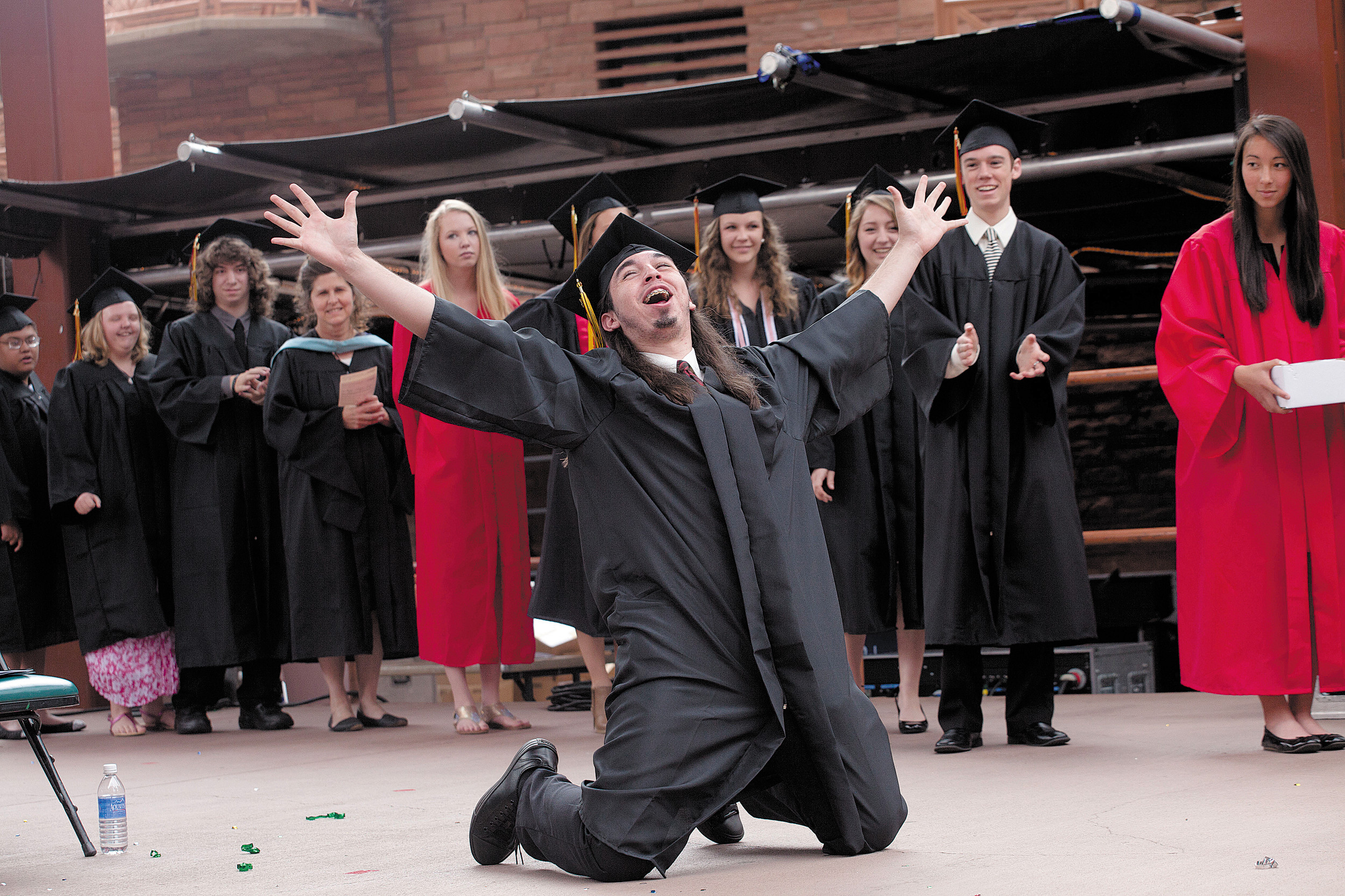 Thomas Rivera drops to his knees after his name is called to receive a diploma during Castle View High School's graduation ceremony at Red Rocks Amphitheater on May 21.
