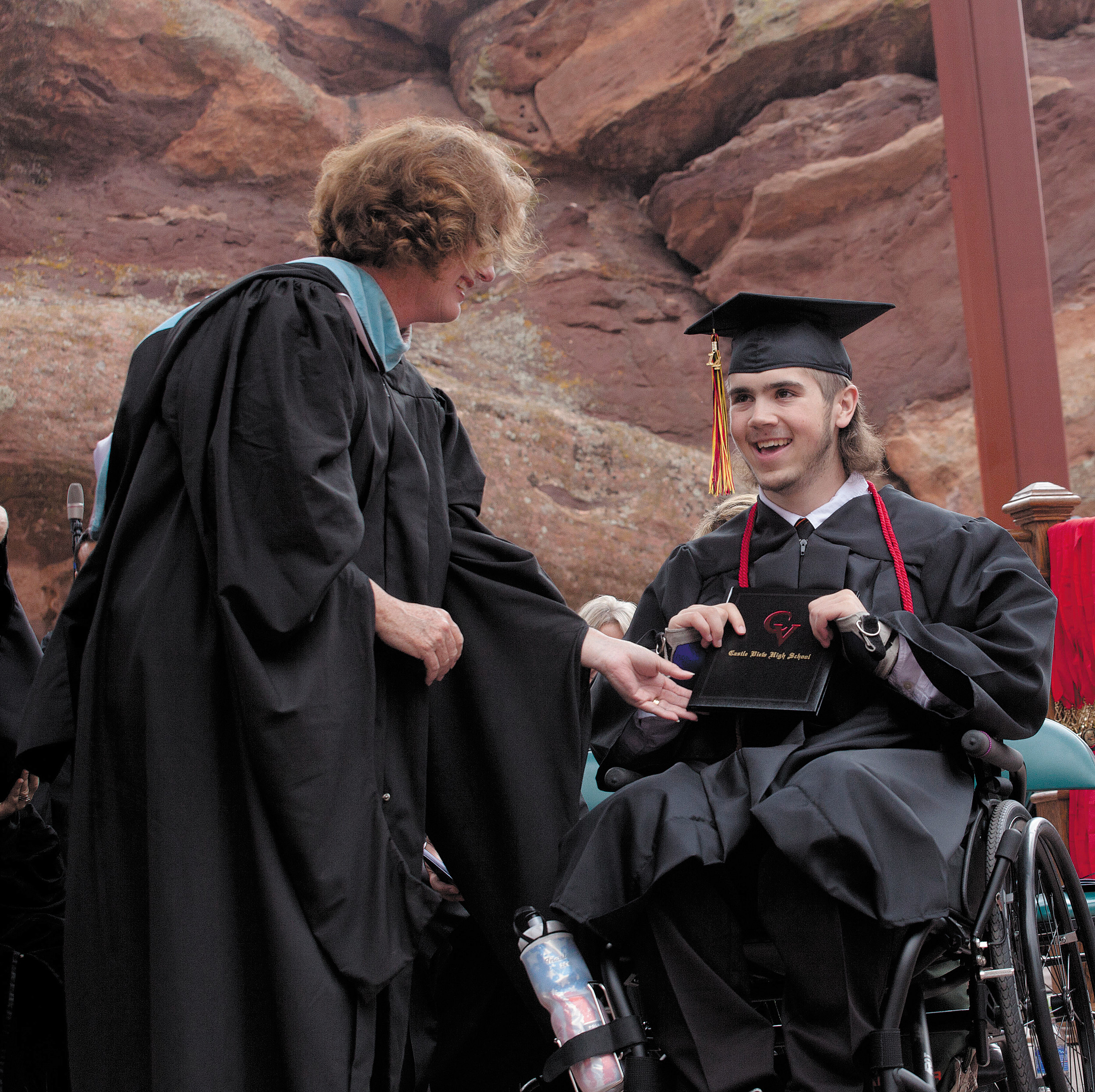 Joseph Hunsaker, the Castle View wrestler who broke his neck during a meet in February, takes his diploma with a smile from DougCo school board director Judith Reynolds during his commencement ceremony on May 21 at Red Rocks Amphitheater.