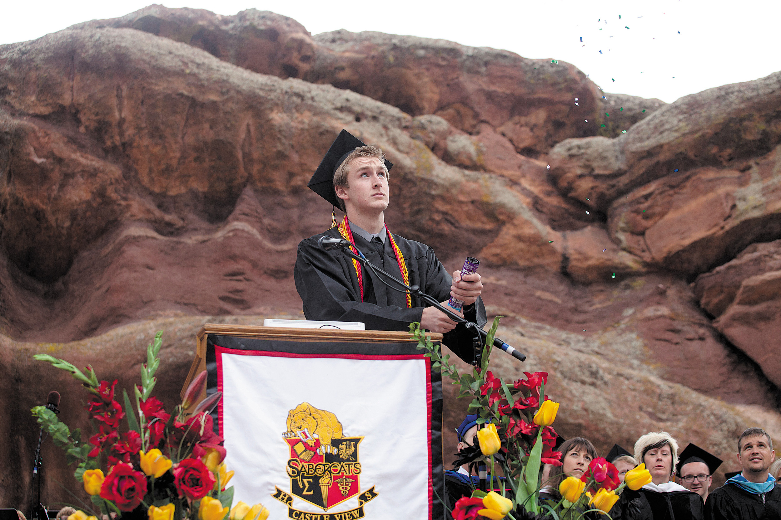Parker Lewis pulls out a confetti popper during his speech for the Biotechnology and Health Sciences Academy at Castle View High School's commencement ceremony at Red Rocks Amphitheater on May 21.