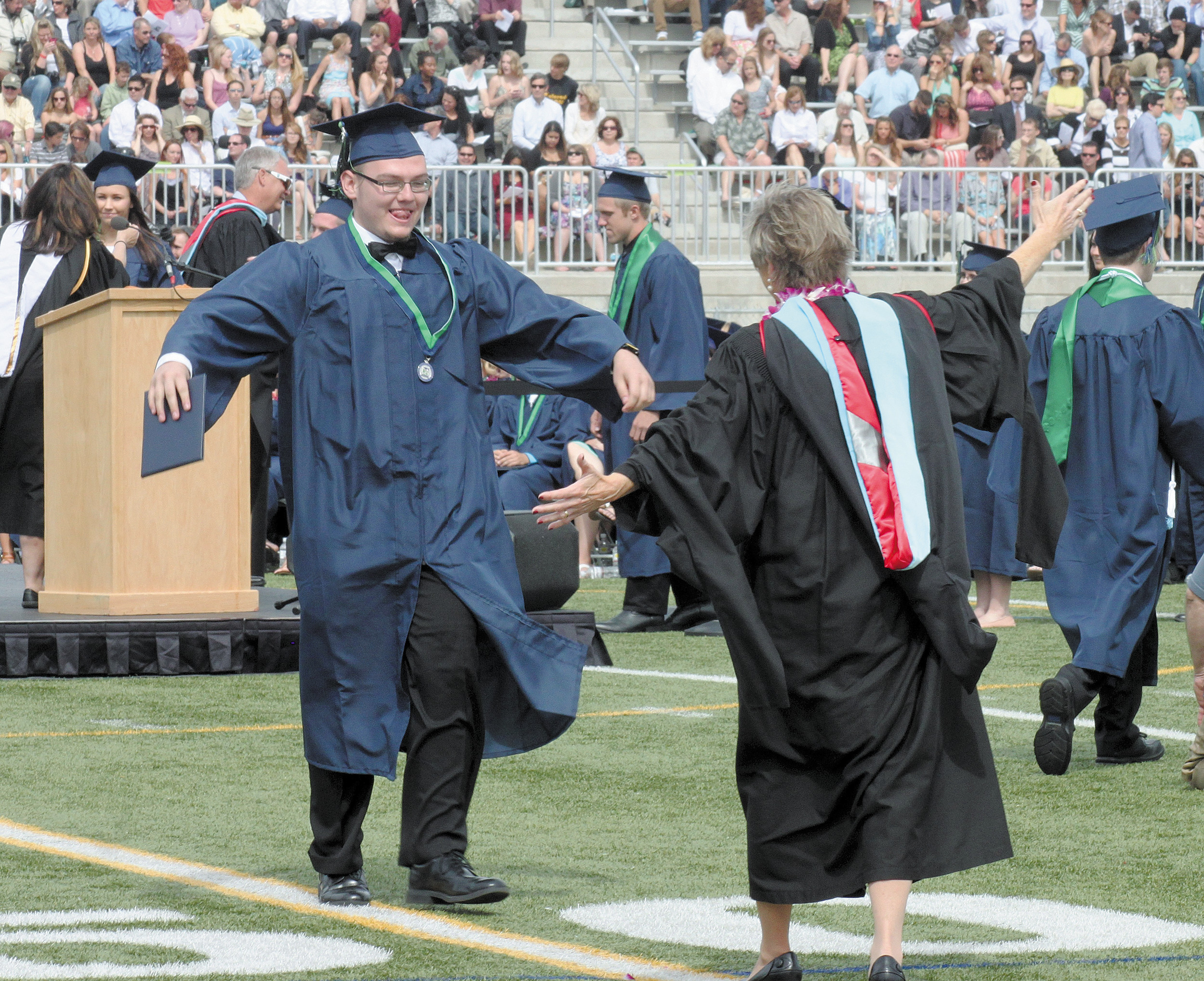 Justin Glidewell gets ready to hug ThunderRidge Principal Carole Jennings after receiving his diploma.