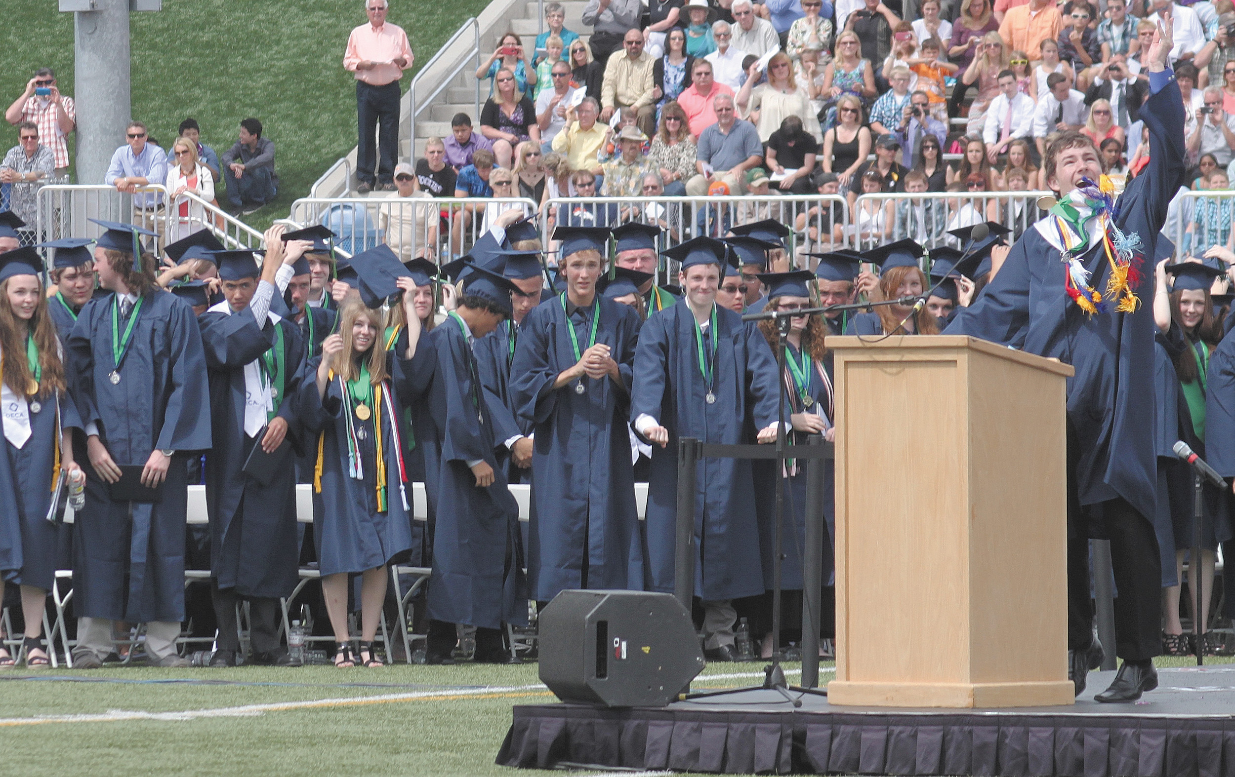Valedictorian James Fair, right, is the first to toss his hat after instructing fellow students to turn their tassels at the end of the May 22 ThunderRidge High School graduation ceremony.