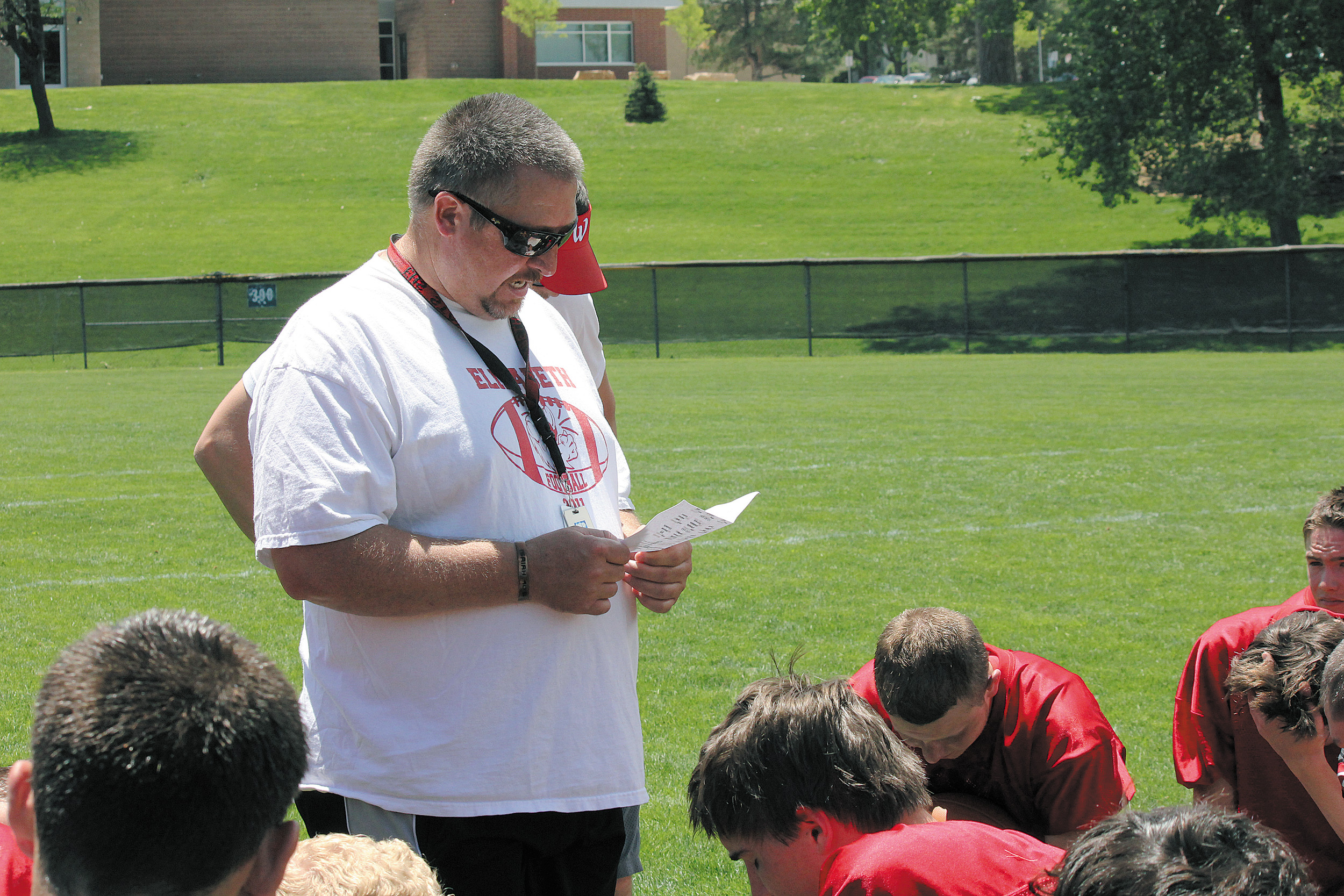 Elizabeth head football coach Chris Cline checks the schedule as he briefs his team about their next game during the 7-on-7 tournament May 31 at Englewood High School. Fifteen teams entered the all-passing competition and the Cardinals battled their way to a fourth-place finish.