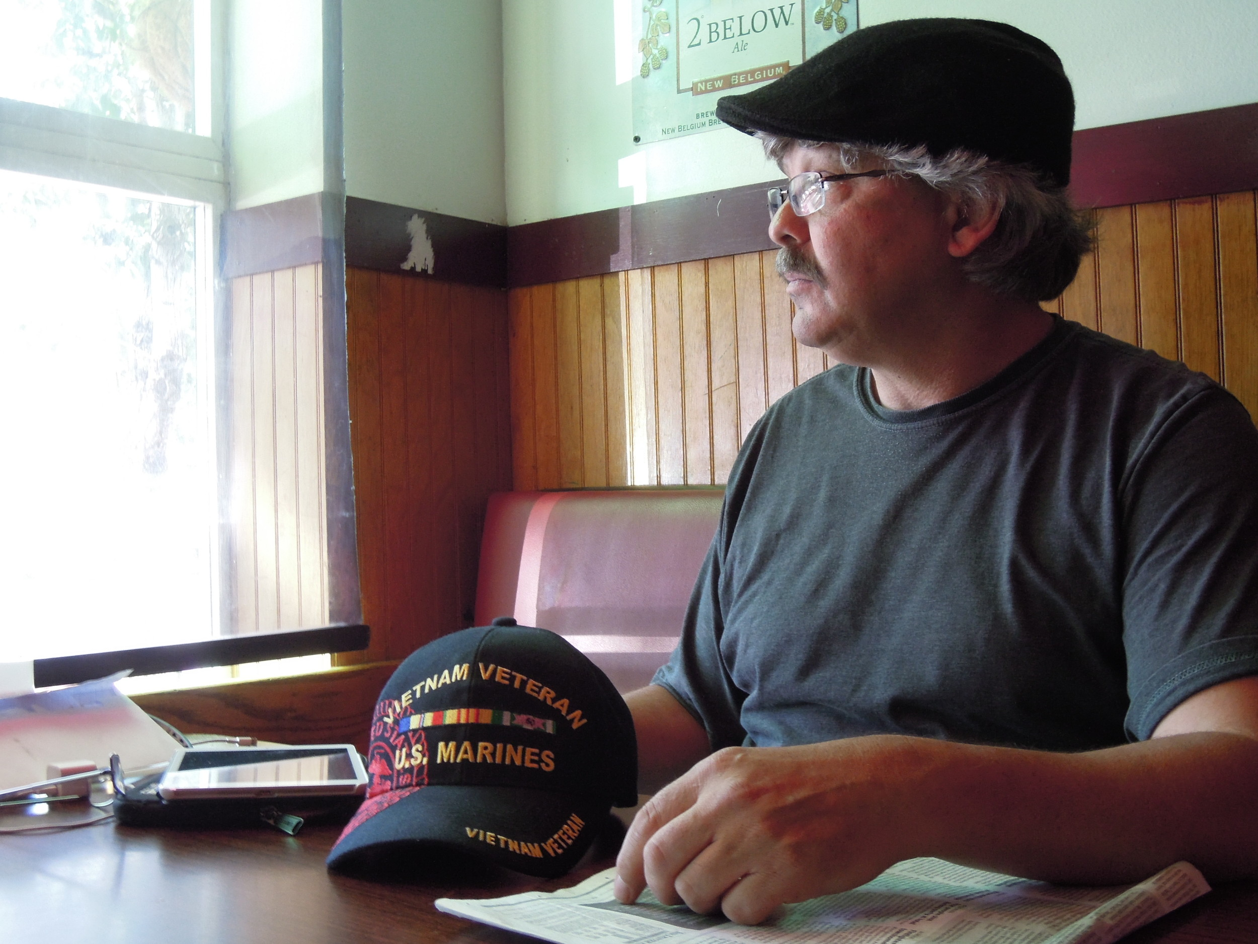 Michael O'Brien thinks about his late friend George Claggett as he sits in a booth inside a bar that Claggett often frequented, Denver's Park Tavern and Restaurant, on June 13. On the table sits the cap that Claggett, a Vietnam veteran, often wore.