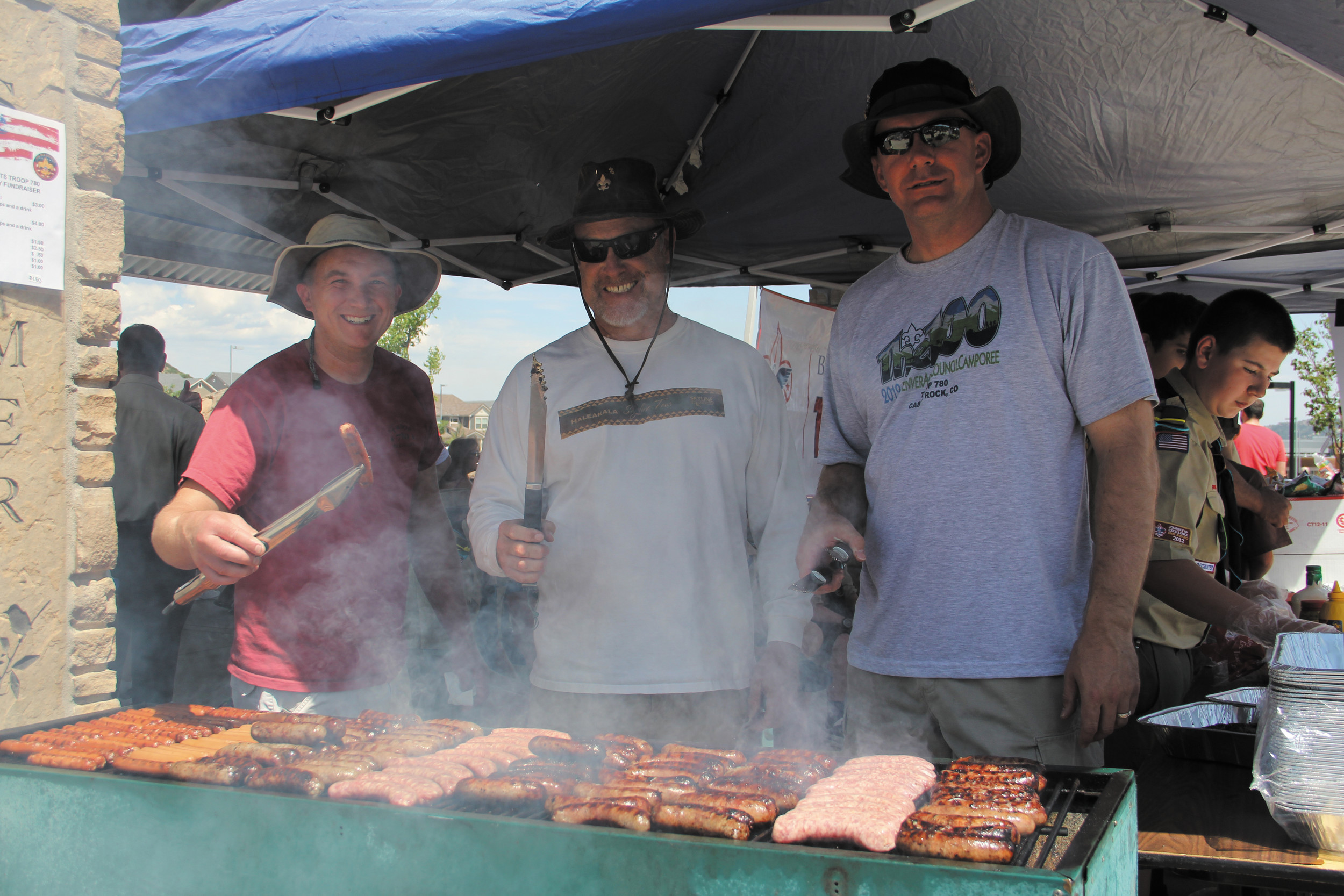 From left, Boy Scout Troop 780 parents Lem Scarborough, Mike Janda, and Jim Nelson grill up some bratwursts and hot dogs as part of the Fourth of July celebration at Bison Park in Castle Rock.