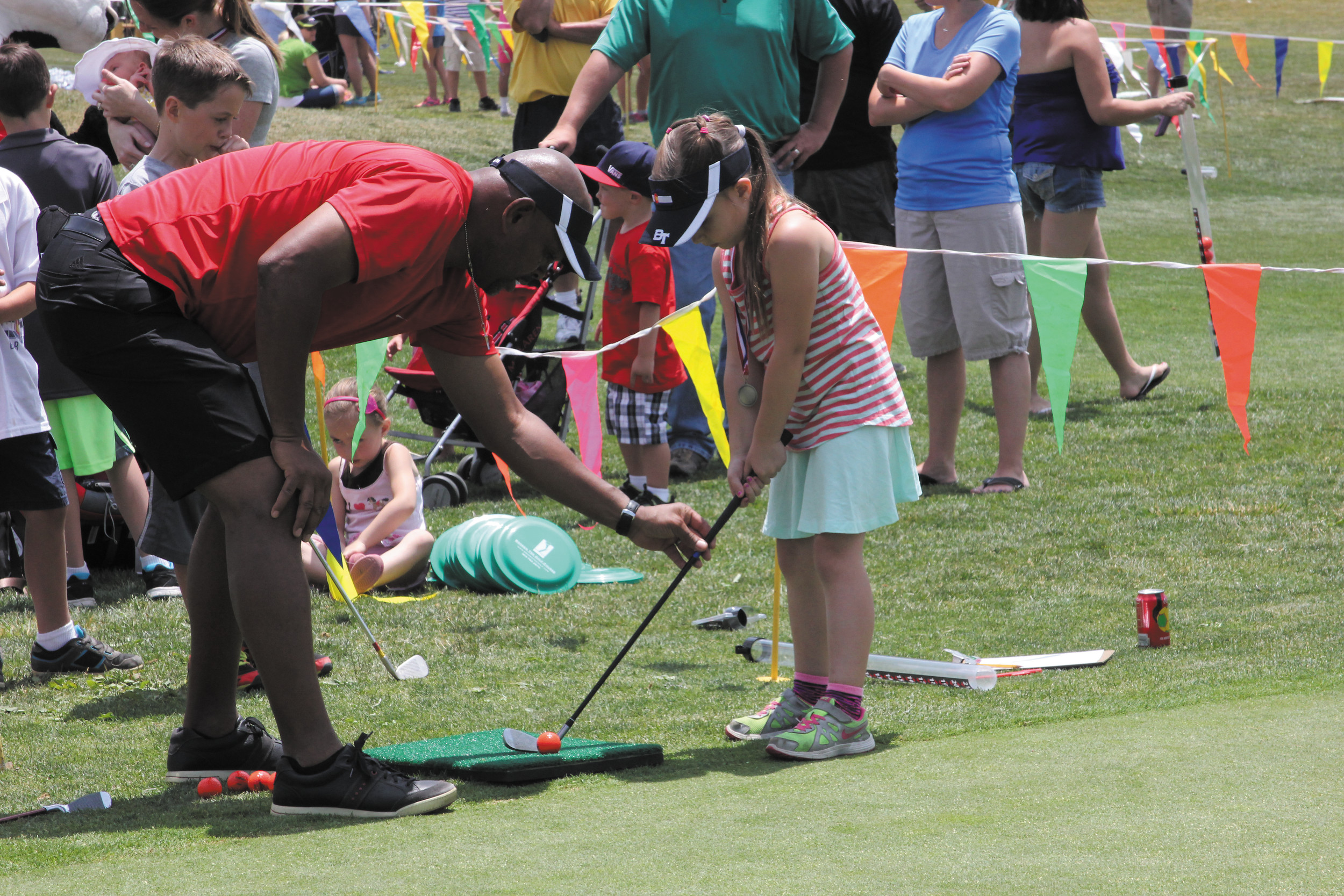 Volunteer David Warden helps Zoe Fortin get the right grip on the club so she can hit the target during the July 2 activities and barbecue wrapping up the Hole-N-One Youth Golf Program that teaches golf fundamentals to 5- to 15-year-olds.  Warden said this is the fifth year he has been a volunteer at the event and it is his way to give back to the community.