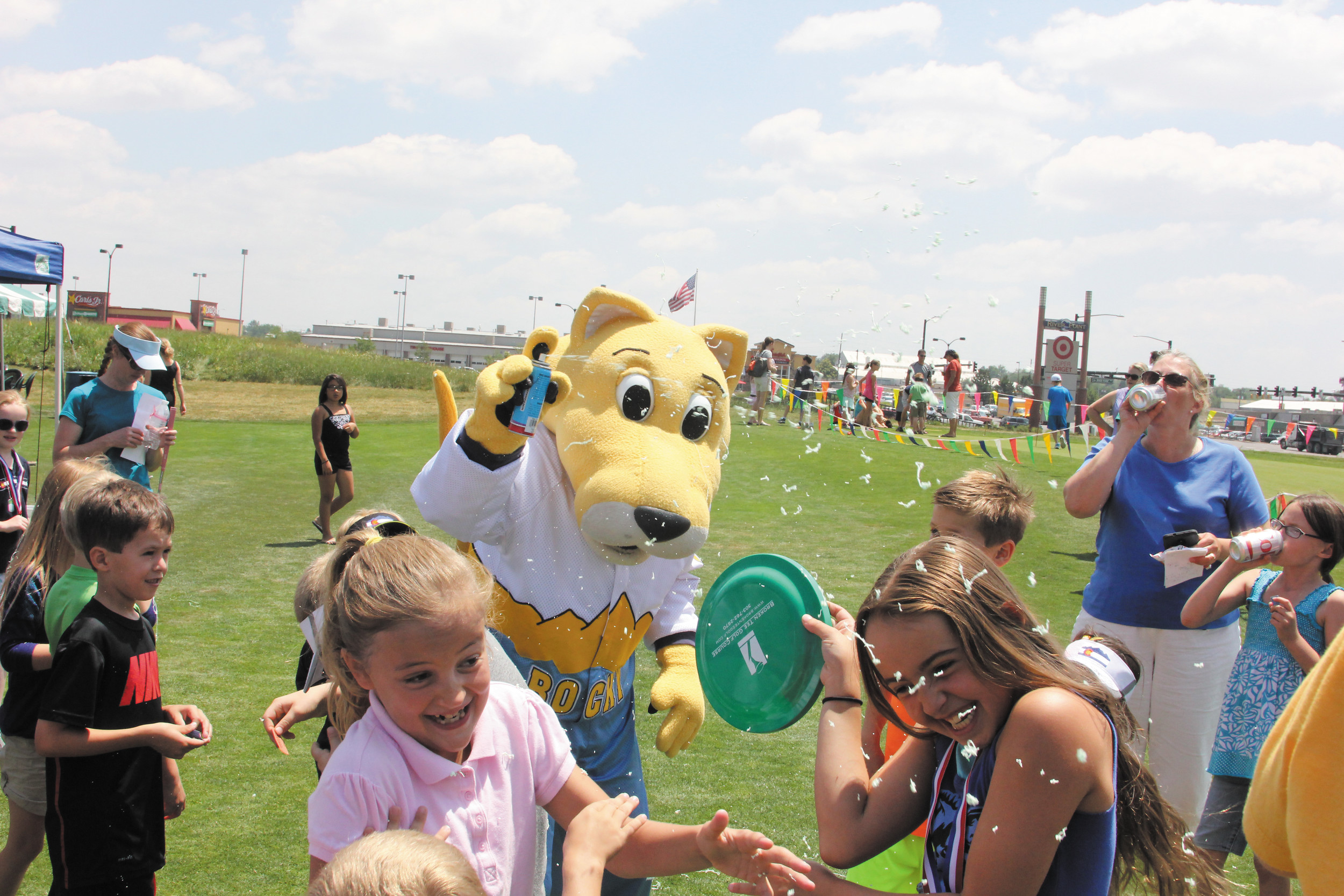 Rocky, the Denver Nuggets mascot, sprays boys and girls with Silly String as he and the children take part in the July 2 activities and barbecue wrapping up the Hole-N-One Youth Golf Program. More than 400 boys and girls attended the Broken Tee at Englewood Golf Course program that marked its13th year teaching golf fundamentals to 7- to 15-year-olds.