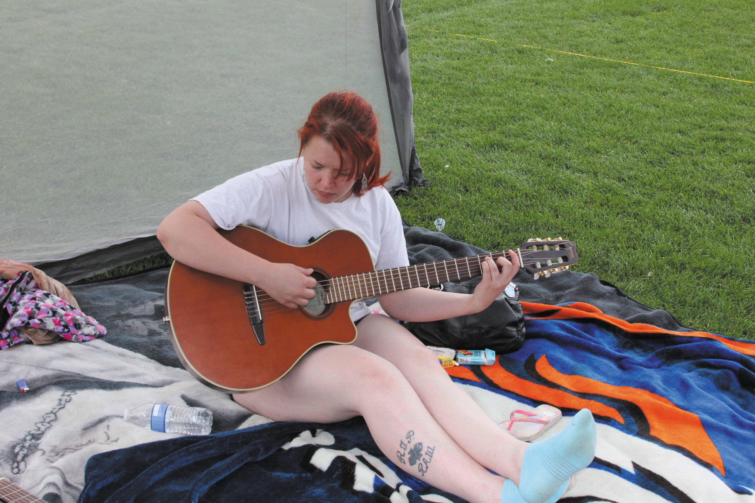 Monica Patton hums and plays her guitar as she takes a break from the other activities at the July 4 Family Fun and Fireworks Event at Cornerstone and Belleview parks. She said she likes to be outside and just play her guitar for her own enjoyment and even occasionally write a song or two.