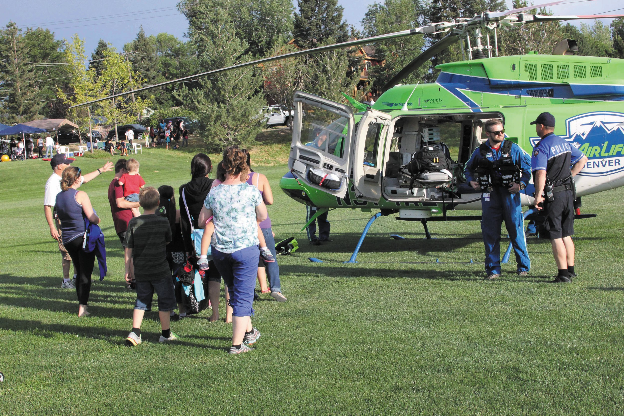 The first group of parents and children are escorted to get an up close look at the AirLife helicopter that landed at Cornerstone Park as part of the Family Fun and Firework festivities. The helicopter was on the ground about an hour so all the people lined up and waiting could get to come out, visit with the crew and look inside the chopper.
