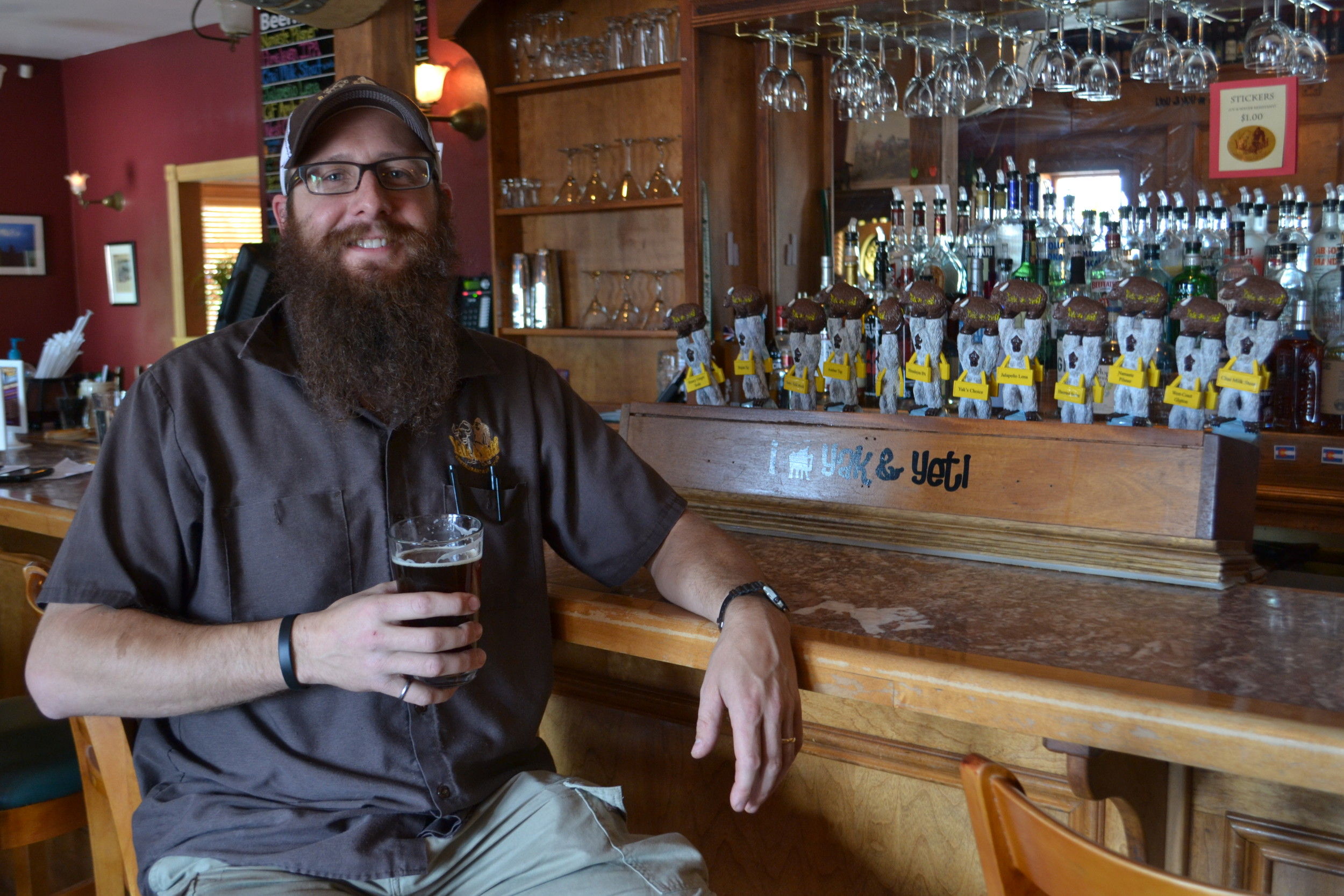 Adam Draeger sits before his selection of beers on tap at the Yak and Yeti.