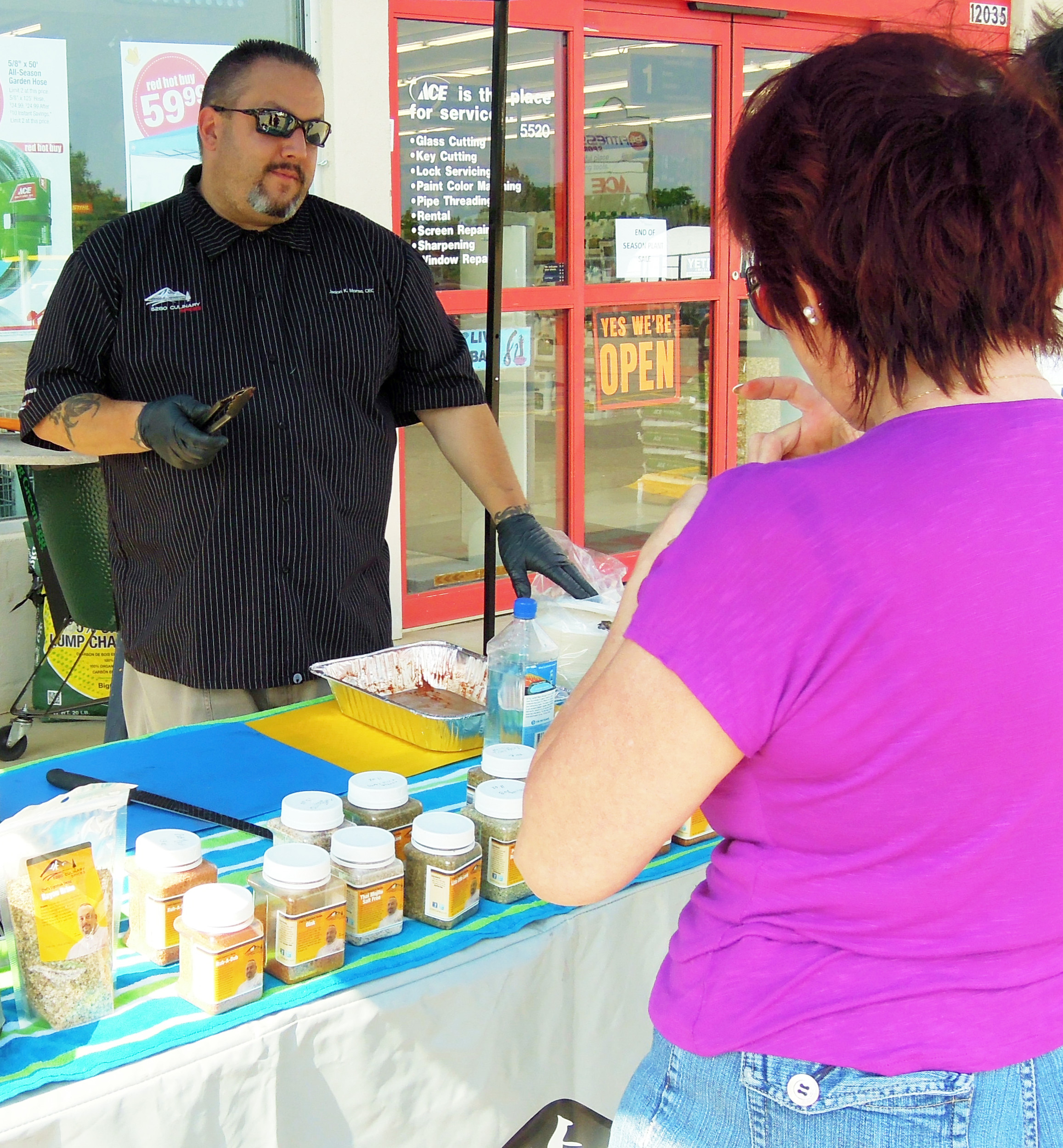 Douglas County School District Executive Chef Jason Morse shared chicken seasoned with his spice mixes with customers, among them Annie Schell, at the Green Mountain Ace Hardware July 8.