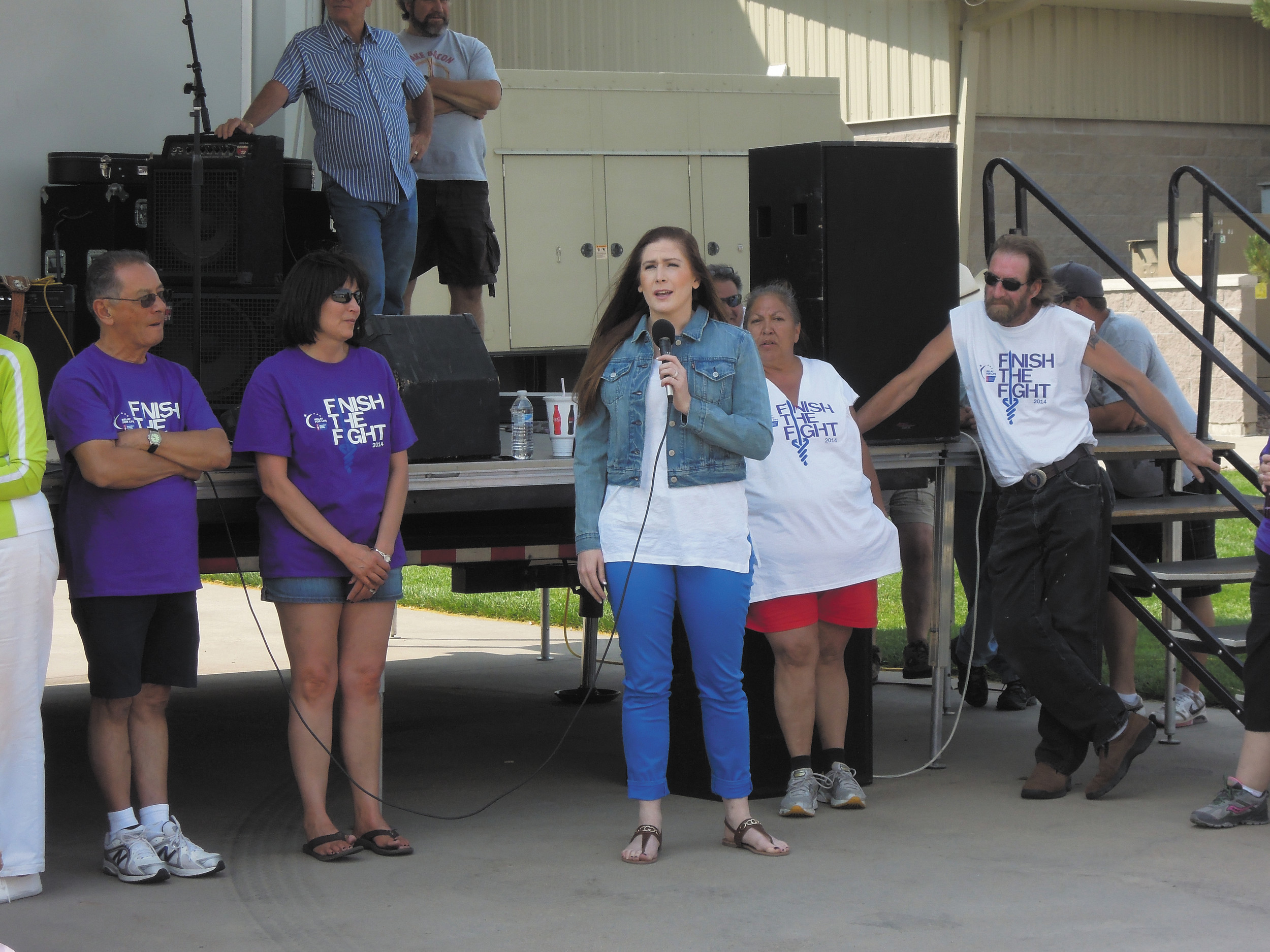 Christina Mullen, along with friend Debbie Hyer (left), addresses walkers at the 2014 Castle Rock Relay for Life at the Douglas County Fair Grounds.
