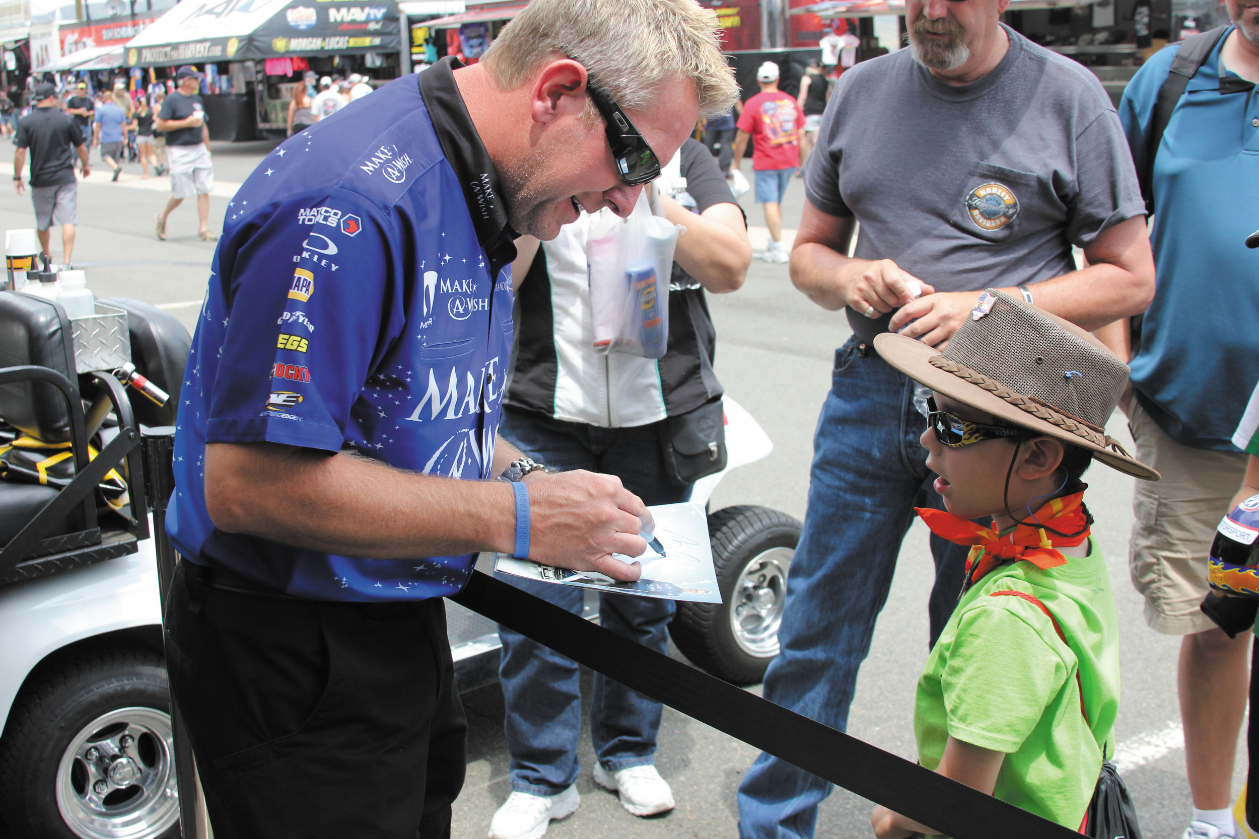 Top fuel funny car driver Tommy Johnson Jr. signs an autograph for Colton Johnson who visited the driver July 18 at the Mile High National Drag Races at Bandimere Speedway in Morrison. Johnson, a former area resident returned to full-time driving this year as the drive with the Make A Wish Foundation team.