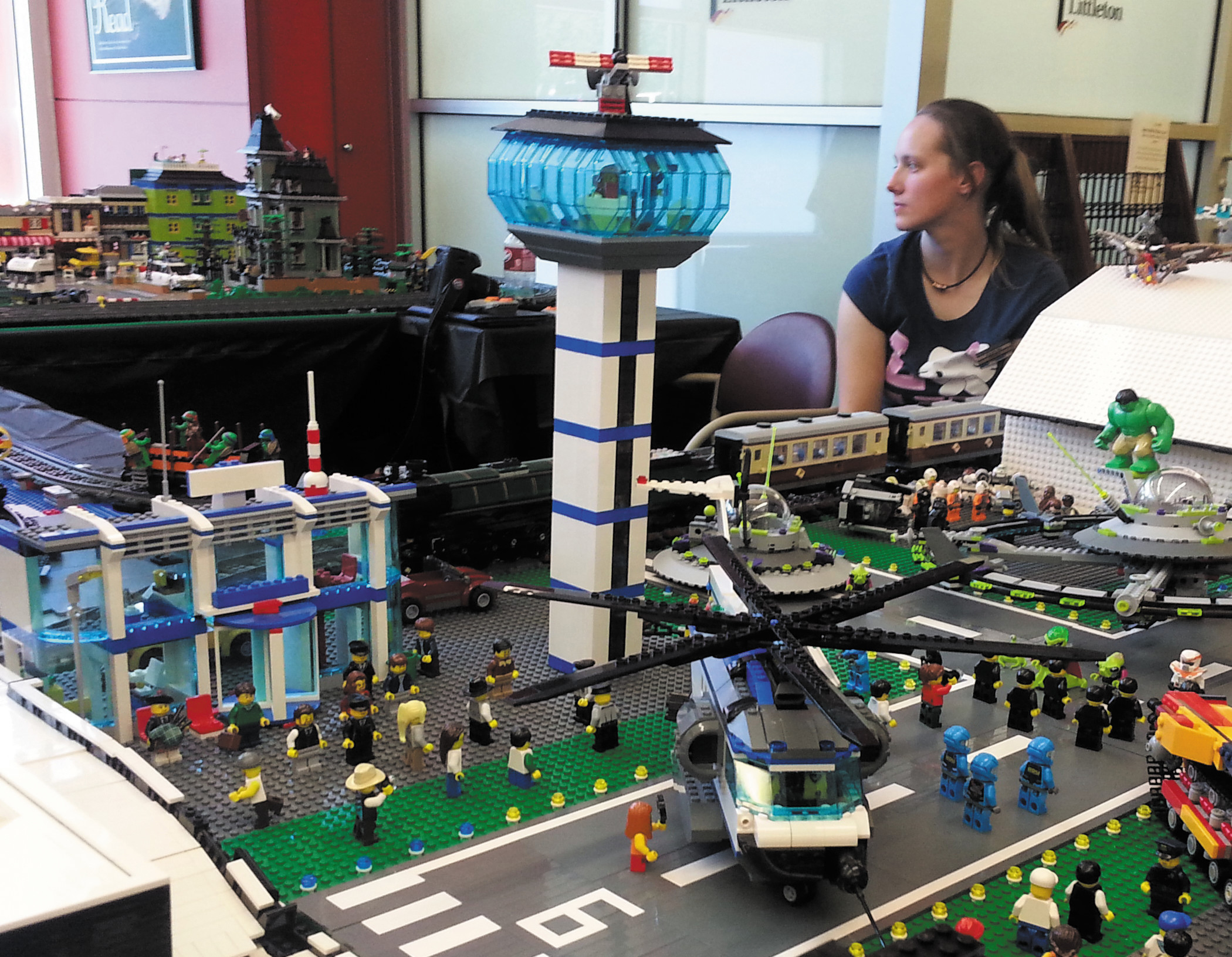 Abby Davis sits surrounded by the Lego land she helped create through her work with the Colorado Lego Users Group.