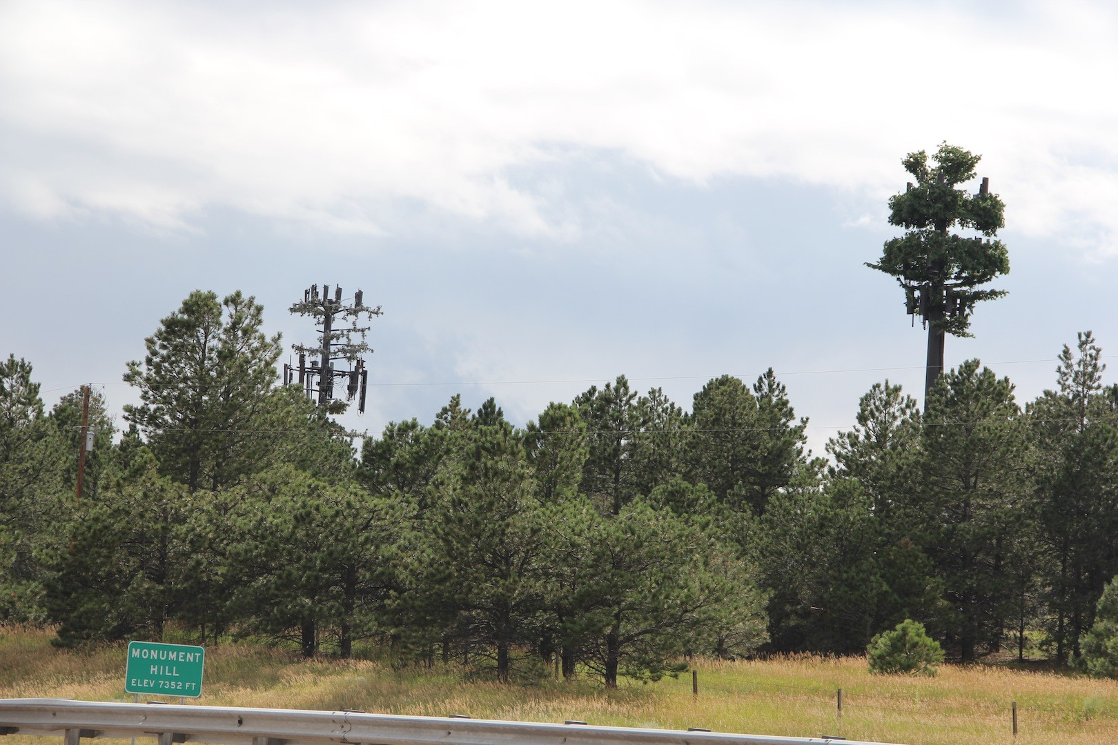 Actually two towers, semi-disguised as tall pine trees, top Monument Hill and can be seen from the road.