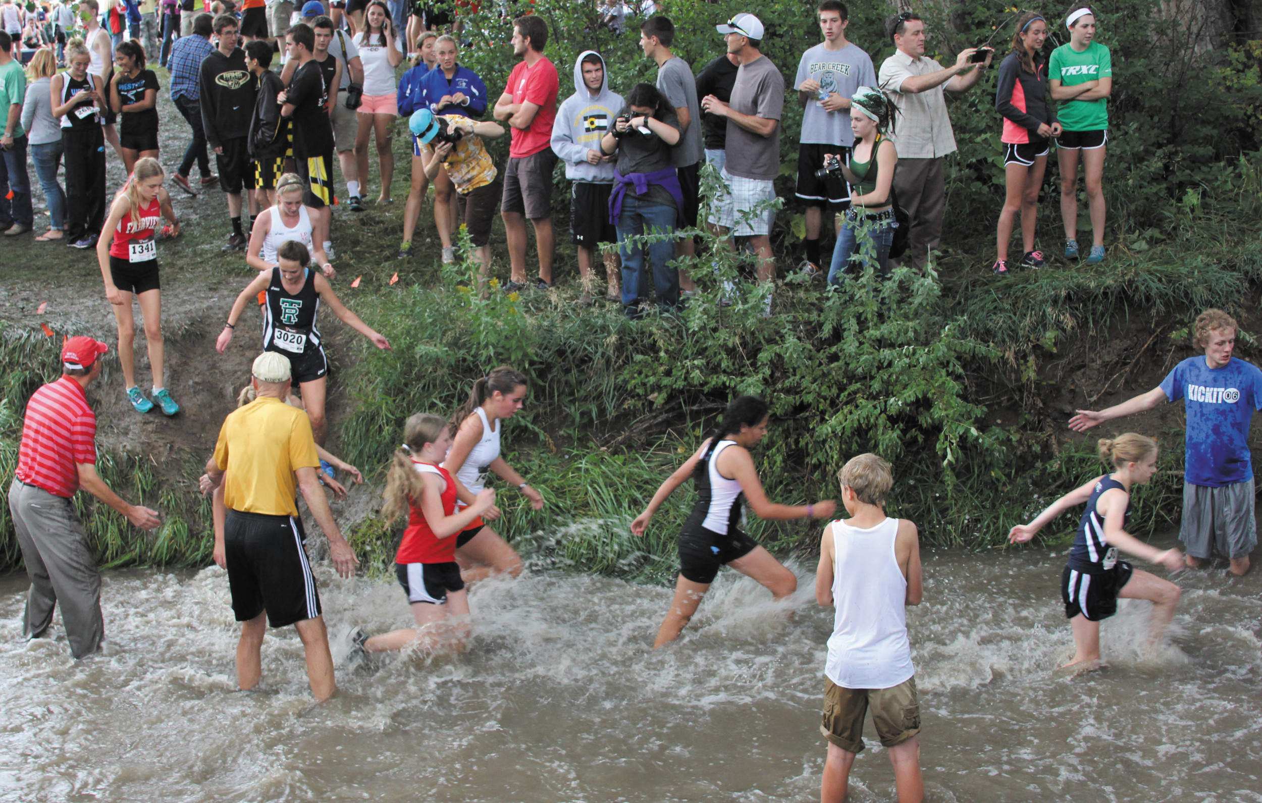 Heavy rains swelled the flow in the High Line Canal, transforming the traditional water jump into a thigh-deep wade through rushing water at the Aug. 29 Warrior Invitational at deKoevend Park. Runners from more than 50 schools overcame the water and muddy slopes to run in the meet.