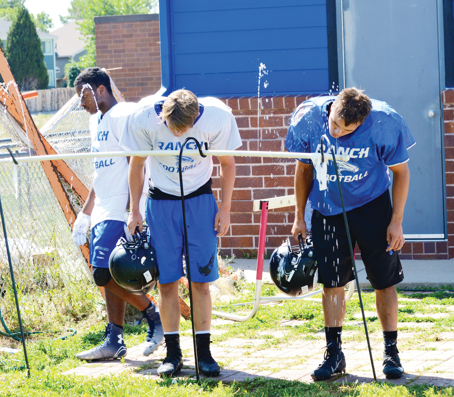 Highlands Ranch High School football players hydrate during a recent practice. Drinking plenty of water and eating the right foods are critical to players' success, coaches and nutrition experts say.
