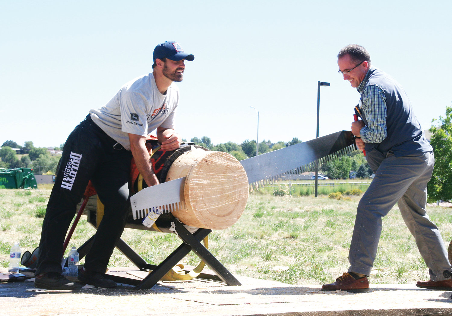 Nathan Waterfield of New York, a professional STIHL Timbersports Series athlete, assists Lonnie Ostransky, the store manager for Duluth Trading Company's newest location in Golden, in sawing a piece of timber during the store's grand opening on Sept. 13, which was celebrated with a lumberjack show.