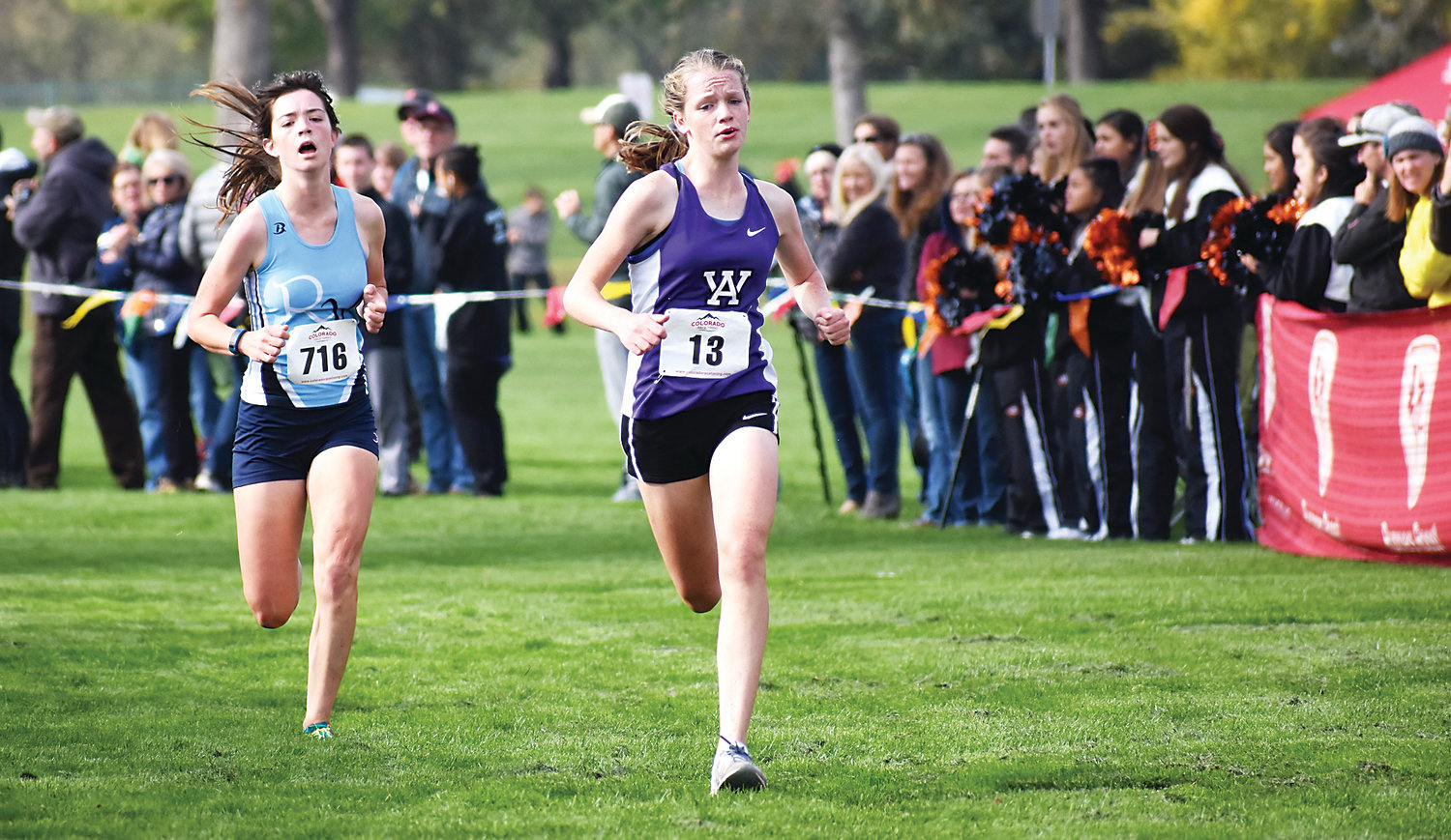 Arvada West freshman Ashlyn Craig (13) and Ralston Valley junior Cassandra Sterns (716) sprint toward the finish line during the Class 5A girls race during the Jeffco League cross country championships Thursday, Oct. 11, at Clement Park. Craig and Sterns both earned first time all-conference honors finishing sixth and seventh. A-West finished second in the team standings while Ralston Valley placed third.