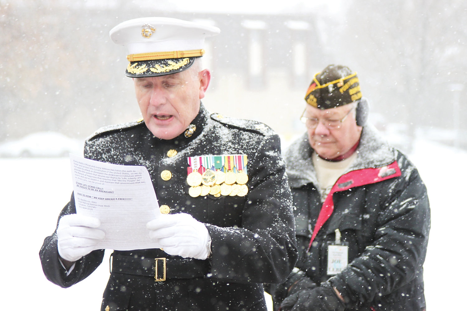 Retired Marine Col. Richard Swedberg, left, reads prepared remarks beside Littleton VFW Post Cmdr. Joe Leber.