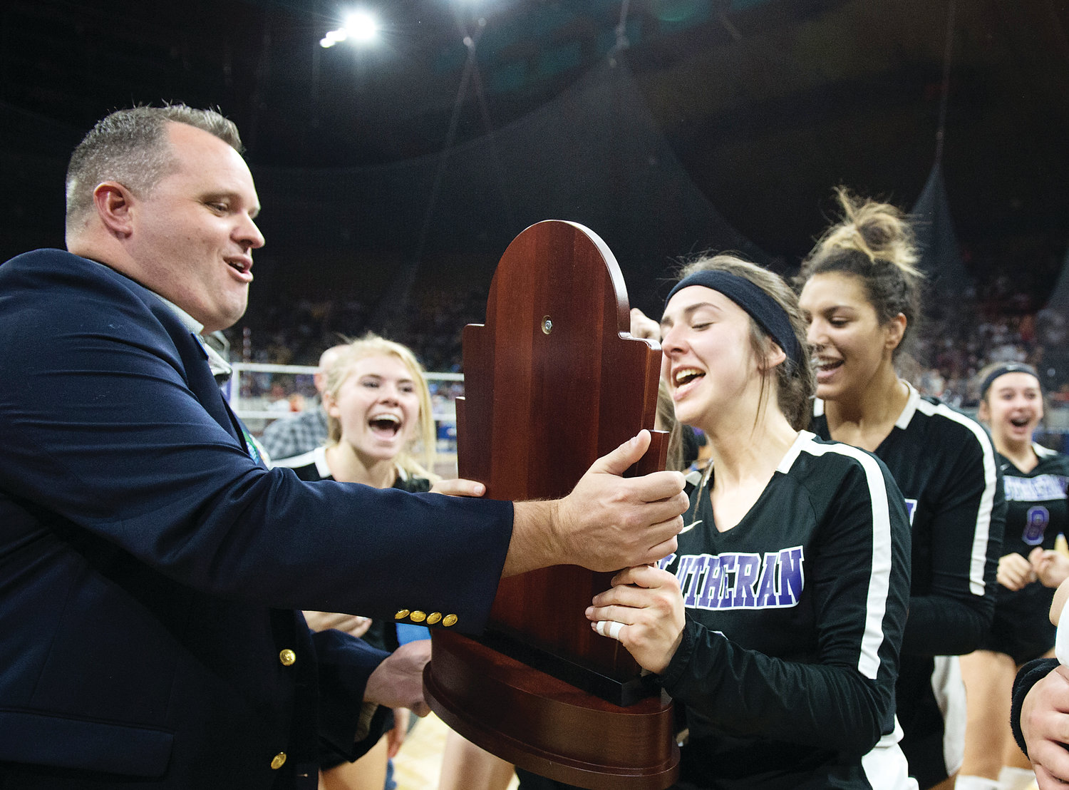 Lutheran's Abby Akers accepts the Championship trophy from CHSAA official Caleb Coates after defeating Colorado Springs Christian 3-1 for the 3A State Final on Nov. 10 at the Denver Coliseum.