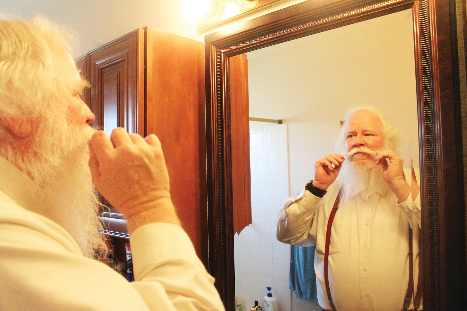 Bryan Austin, 60, primps his mustache before a Nov. 9 Christmas party hosted by a local Mothers of Preschoolers group. It takes about 30 minutes for Austin to sculpt his beard and mustache to look like Santa's.