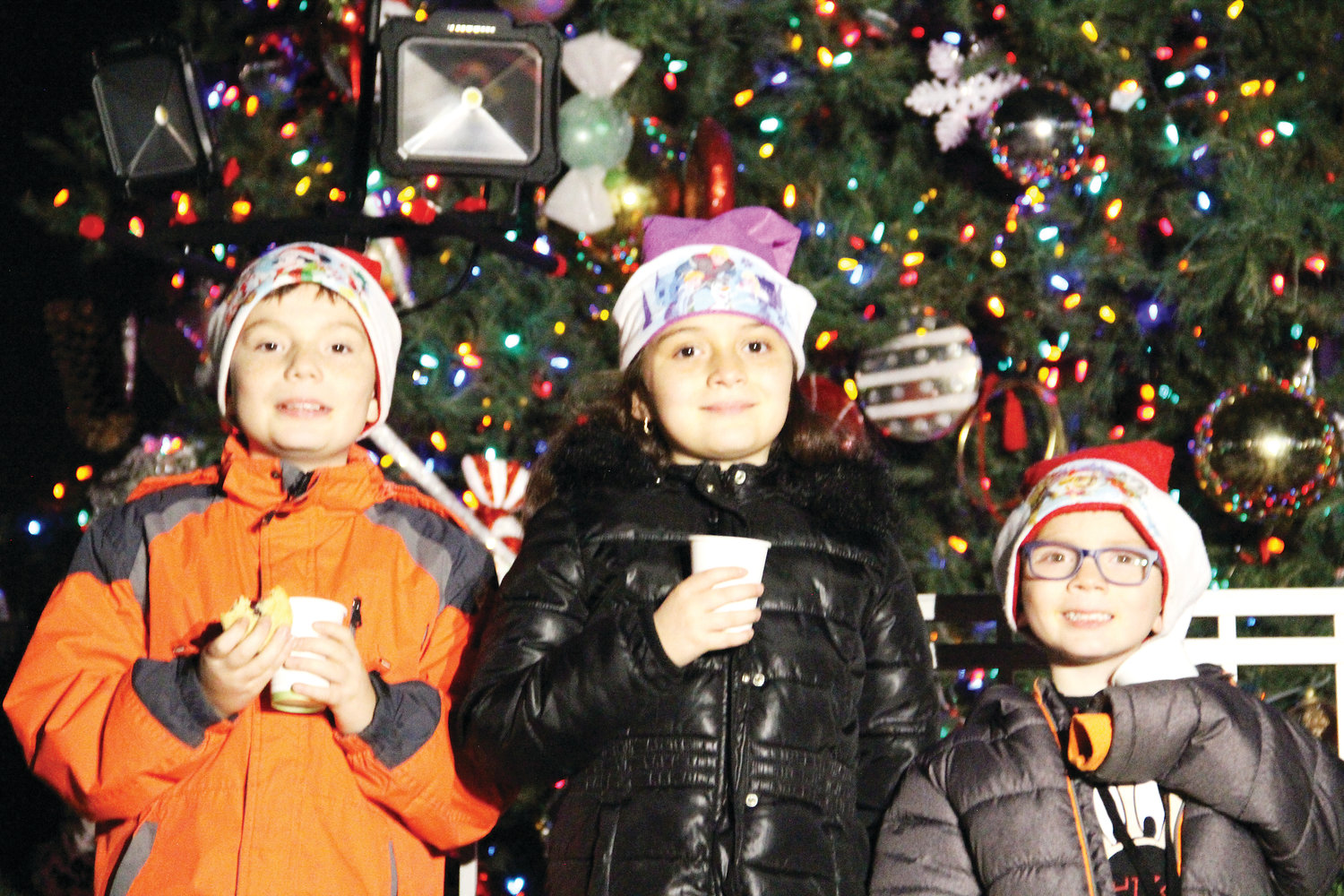 From left, Afrain Iniguez, 10; Sofia Iniguez, 8; and Pedro Iniguez, 5, pose for photos in front of the Christmas tree at the Englewood Civic Center Dec. 1 at the Englewood Holiday Concert. Below: The Christmas tree, more than two dozen feet tall, in front of the Englewood Civic Center Dec. 1 at the Englewood Holiday Concert.