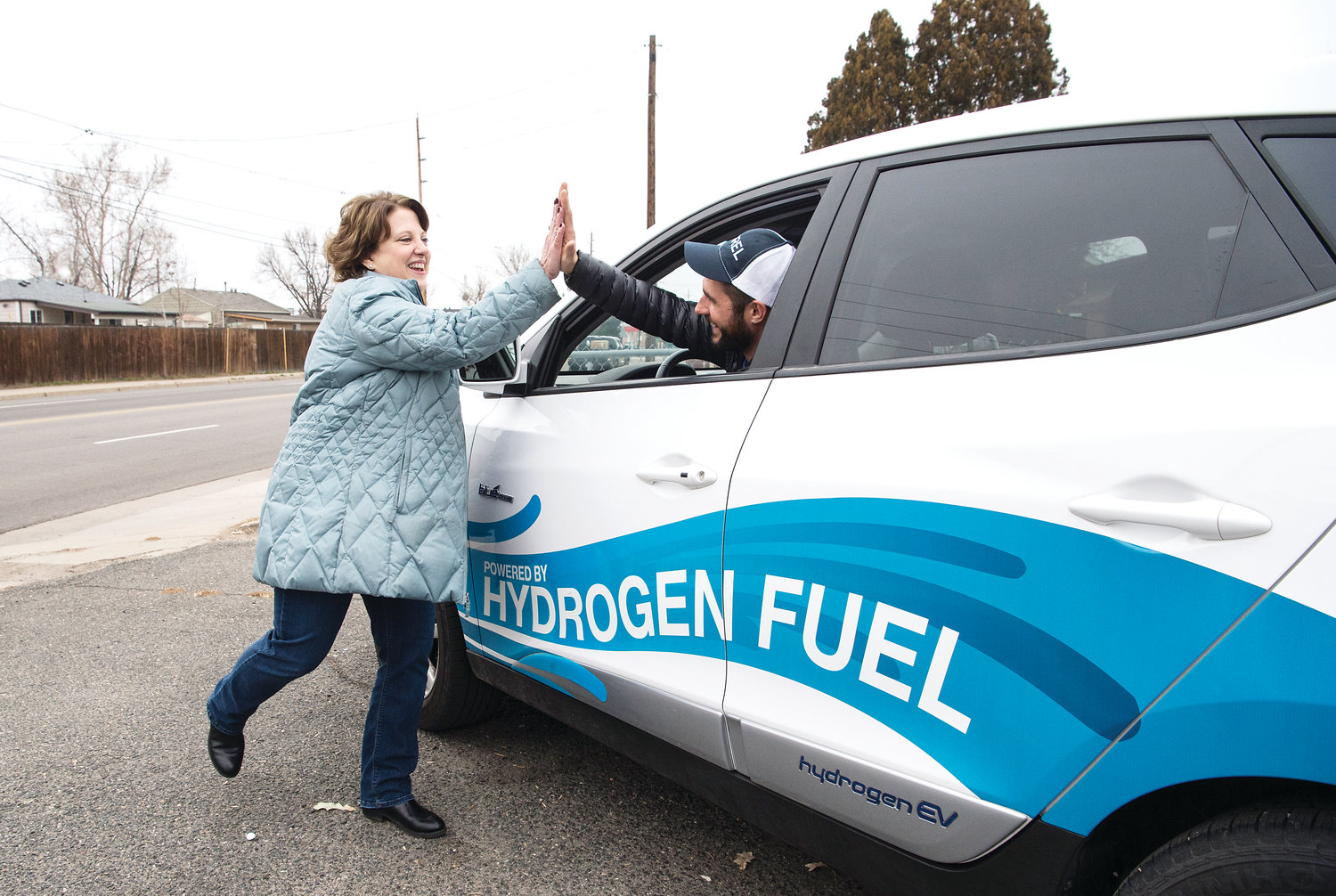 National Renewable Energy Laboratory (NREL) employee Angie Rhyne gives a high-five to her colleague Shaun Onorato following a delivery to a Project Angel Heart client on Nov. 30. Onorato is sitting inside a Hyundai Tucson — one of the two Hydrogen Fuel Cell vehicles that the NREL employees used to deliver food that day.