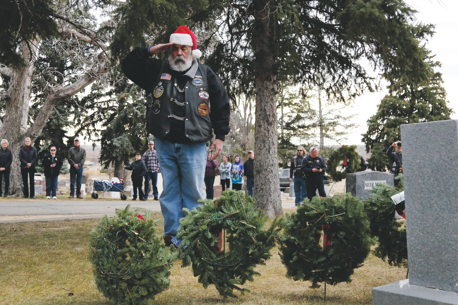 Bruce Weller, U.S. Navy veteran, salutes after placing a wreath in honor of the 93,129 U.S. servicemen from all branches of service whose last known status was either prisoner of war or missing in action.